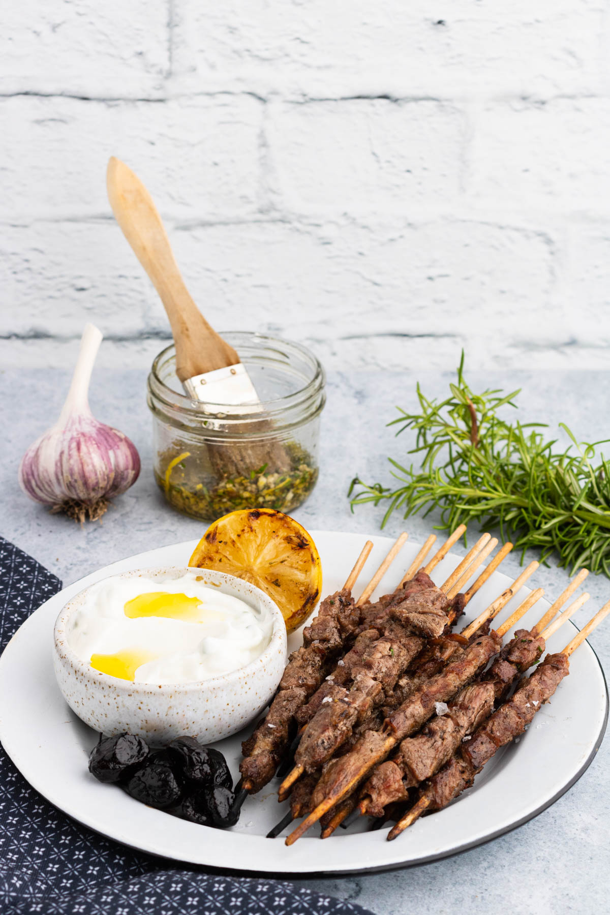 White platter with grill spiedini skewers, tzatziki grilled lemon and prunes.