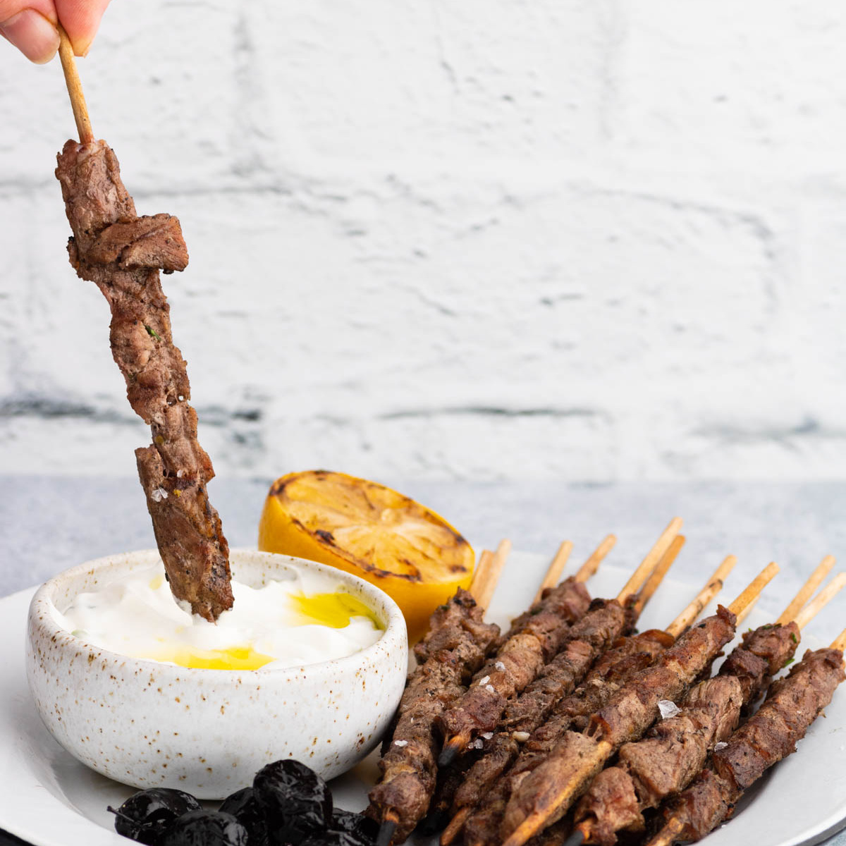 Grilled spiedini skewers on a white plate with one skewer being dipped into the tzatziki sauce