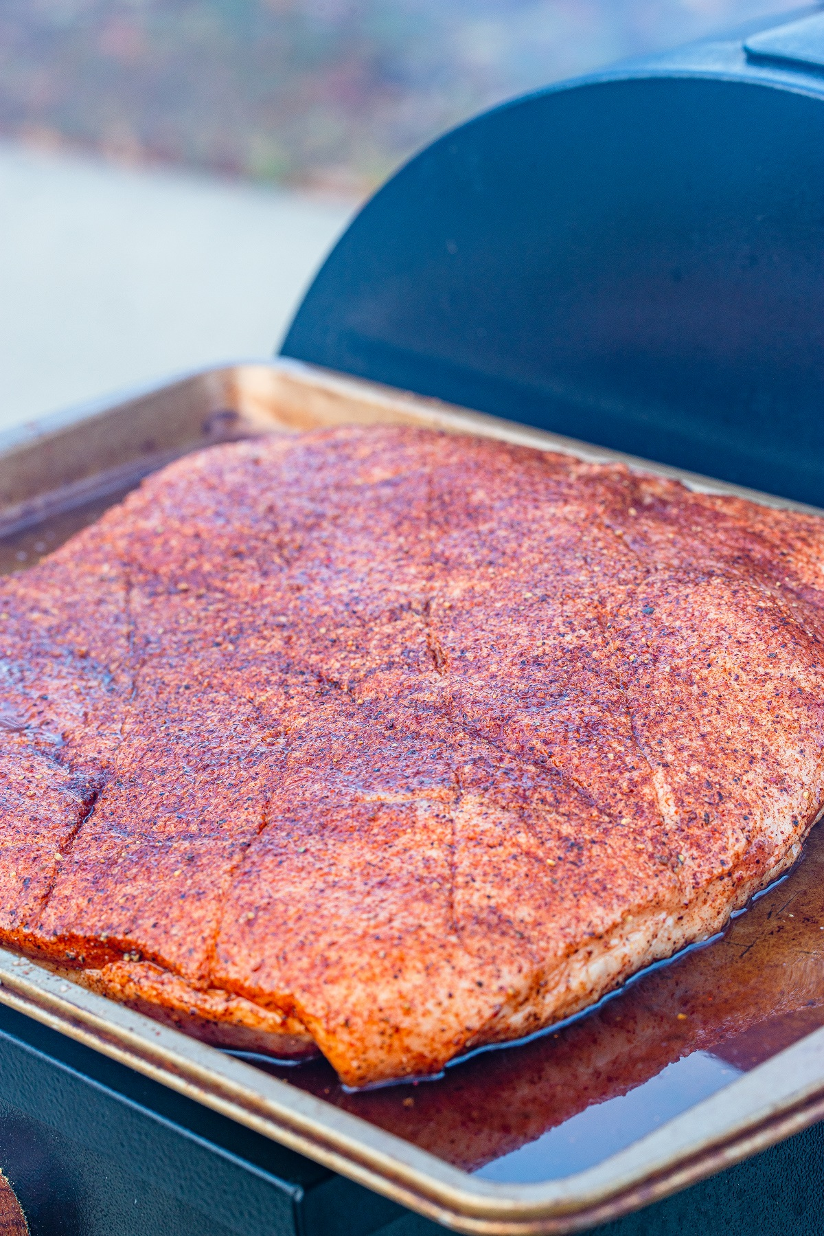 Pork belly after it has been dry rubbed and refrigerated and is ready to go into the smoker.