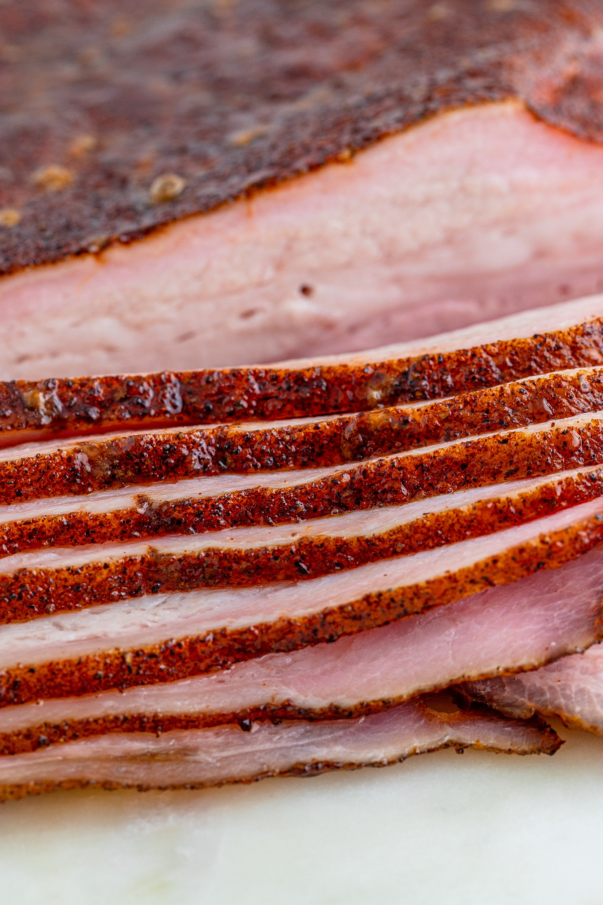 Close up picture of slices of smoked pork belly and the dry rub crust.
