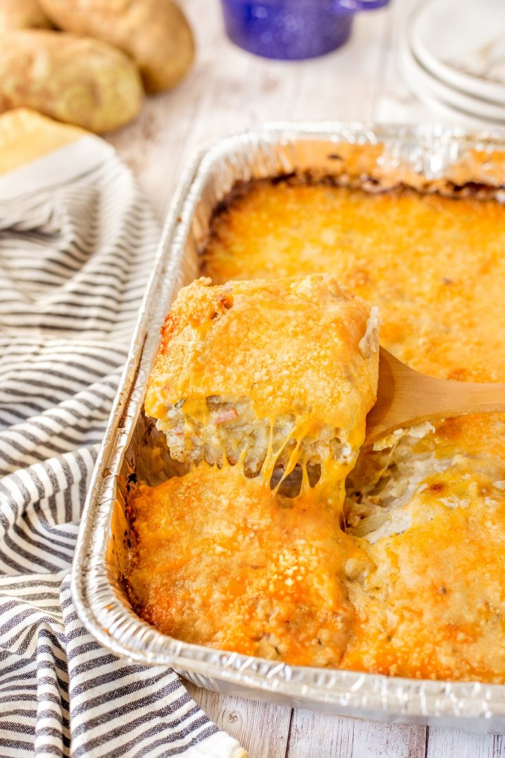 A square serving of smoked scalloped potatoes with ham being lifted out of a foil pan.