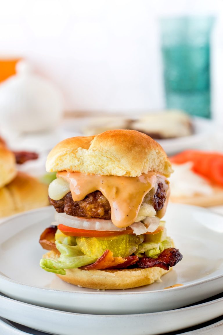 Beef sausage slider on a bun sitting on a white plate with pickle bacon, lettuce onion, cheese and donkey sauce.