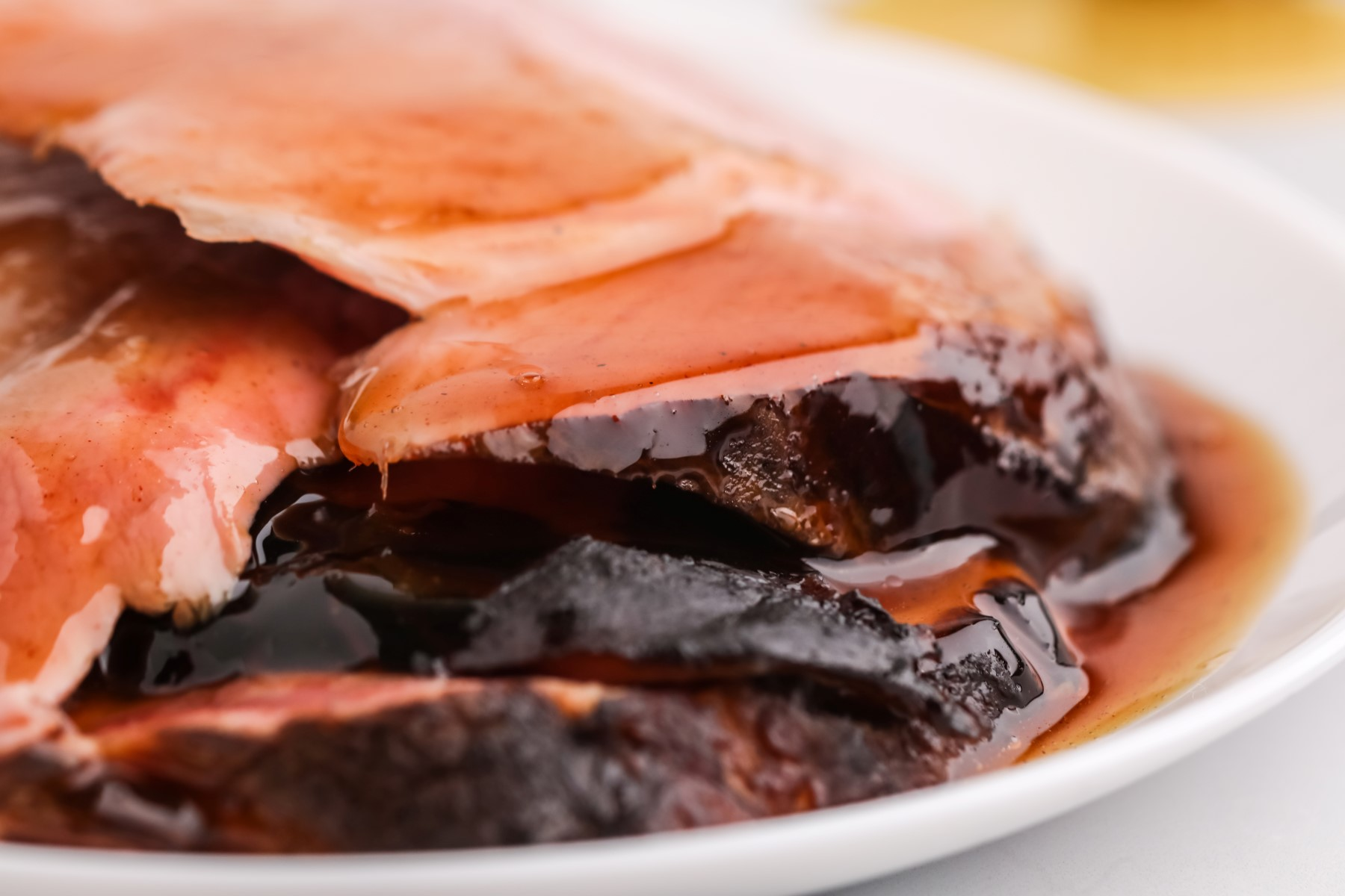Slices of smoked ham on a white plate covered in the brown sugar honey sauce.