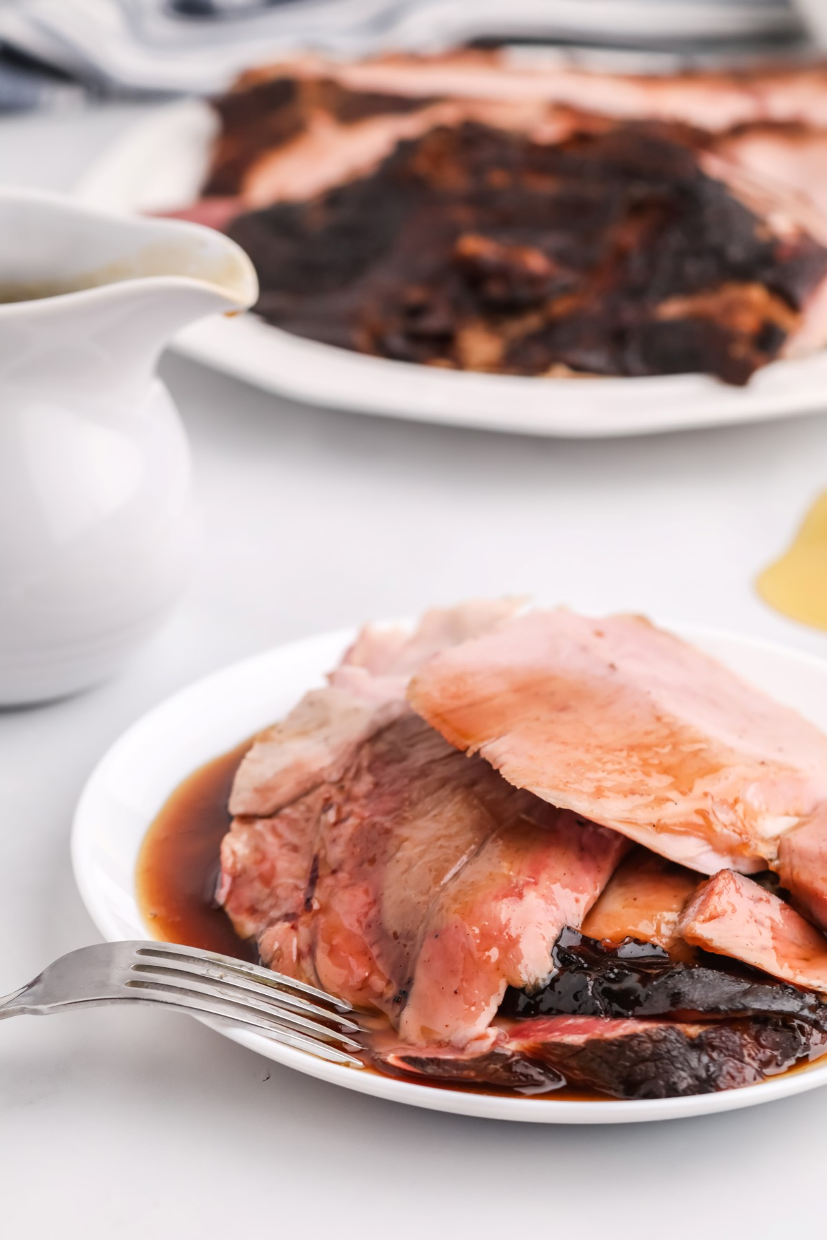 Sliced smoked ham on a white platter covered with brown sugar honey sauce with a fork