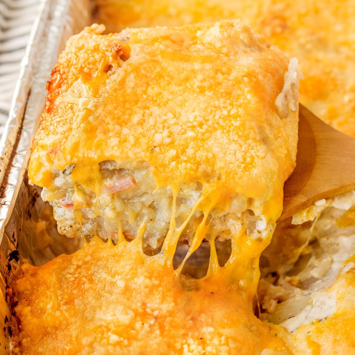 Slice of Smoked Scalloped Potatoes with Ham being lifted out of the pan with a wooden spoon