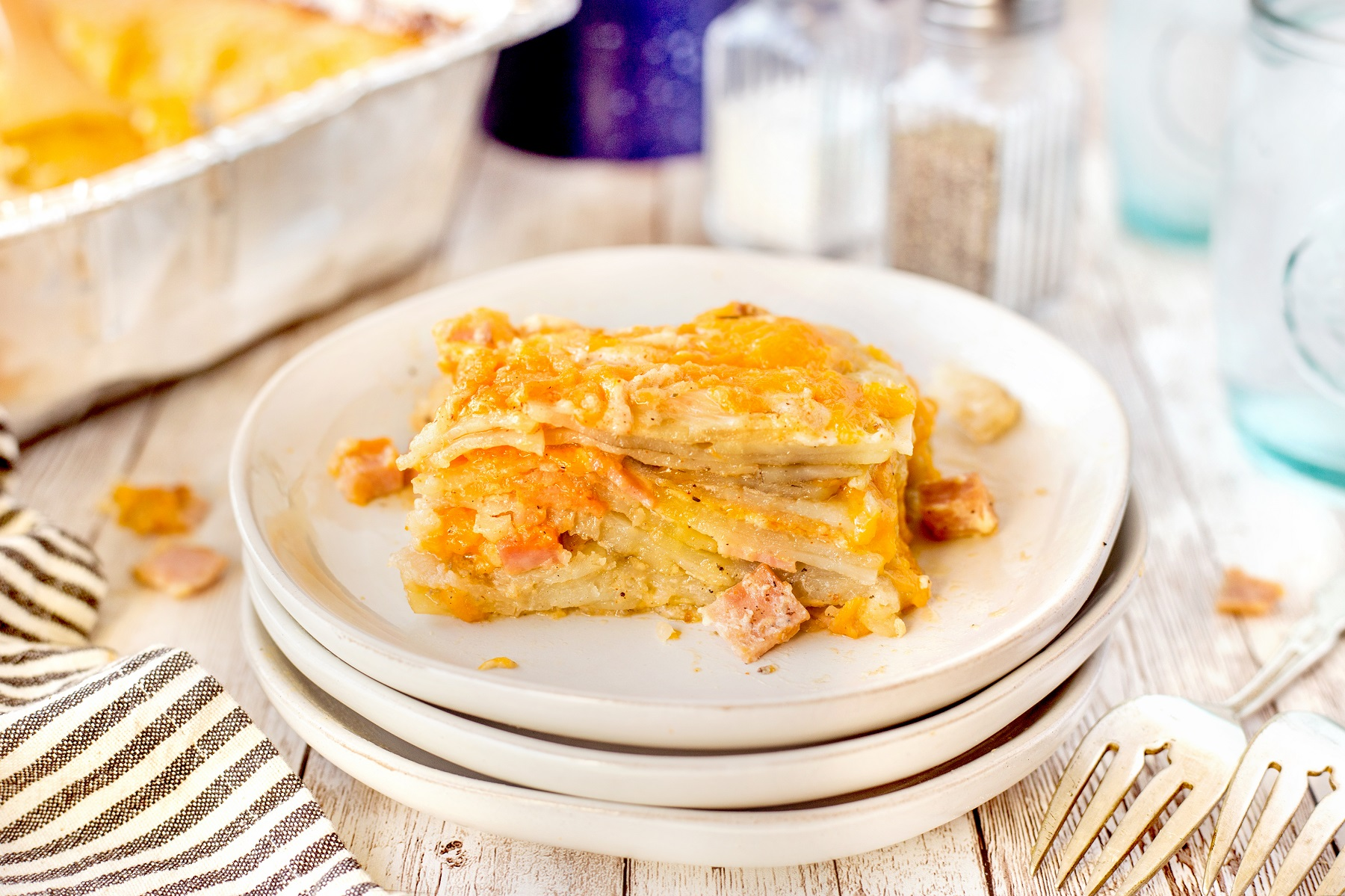 Square of smoked scalloped potatoes with ham on a white plate with forks beside the plate