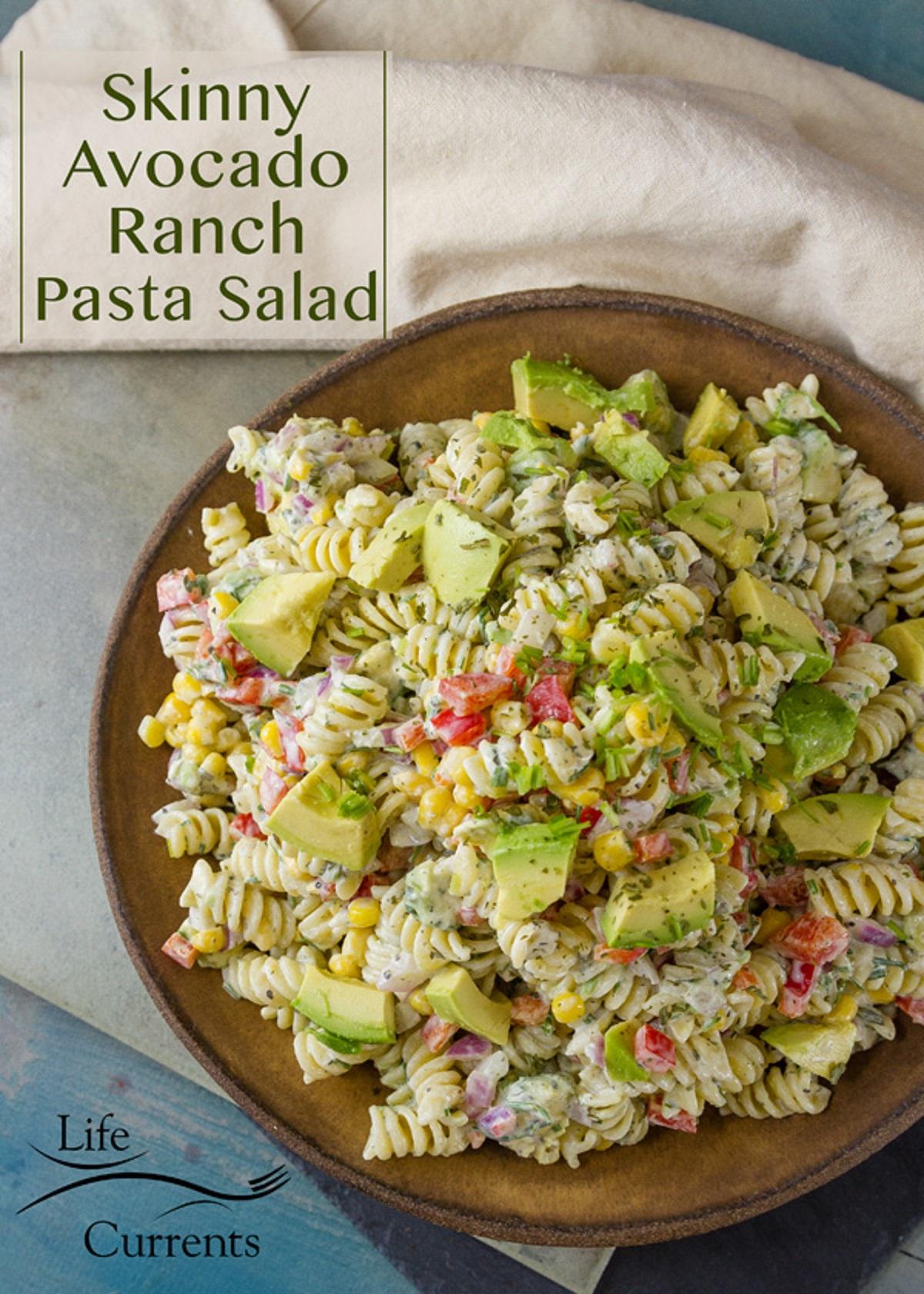 Avocado ranch pasta salad in a brown ceramic bowl.