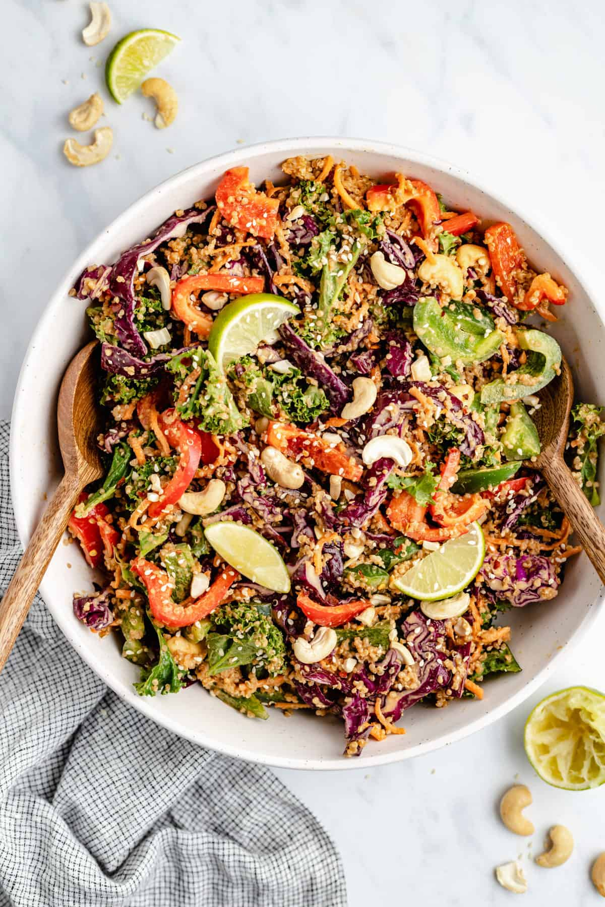Cashew Thai quinoa salad in a white serving bowl with wooden serving spoons
