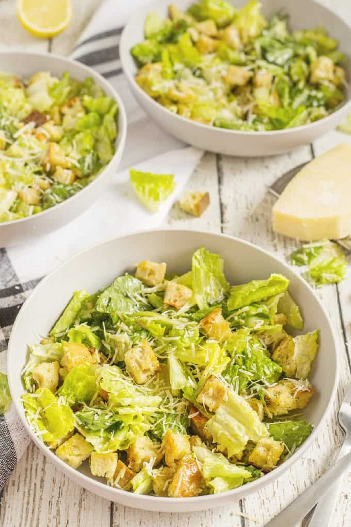 Classic Caesar salad with grated parmesan and croutons  in a white bowl