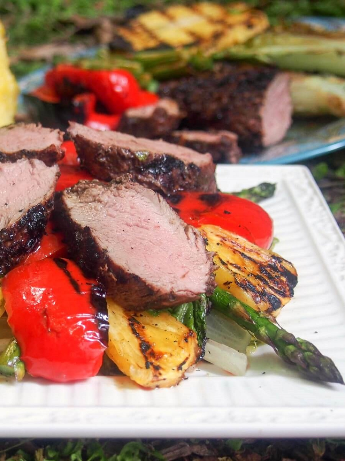 Grilled pork and pineapple salad with asparagus on a white platter
