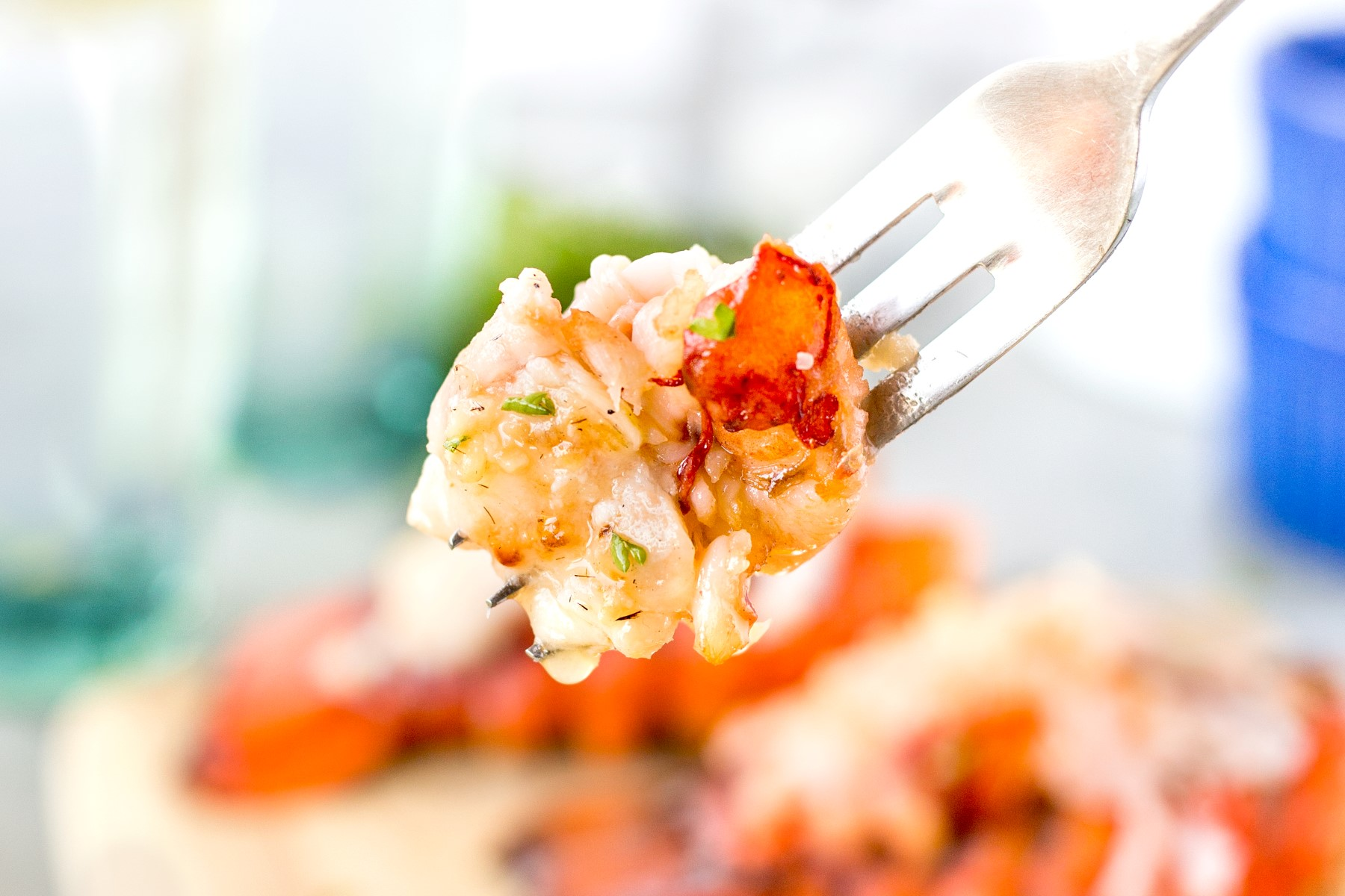 Fork with a large bite of grilled lobster meat dripping with melted butter.