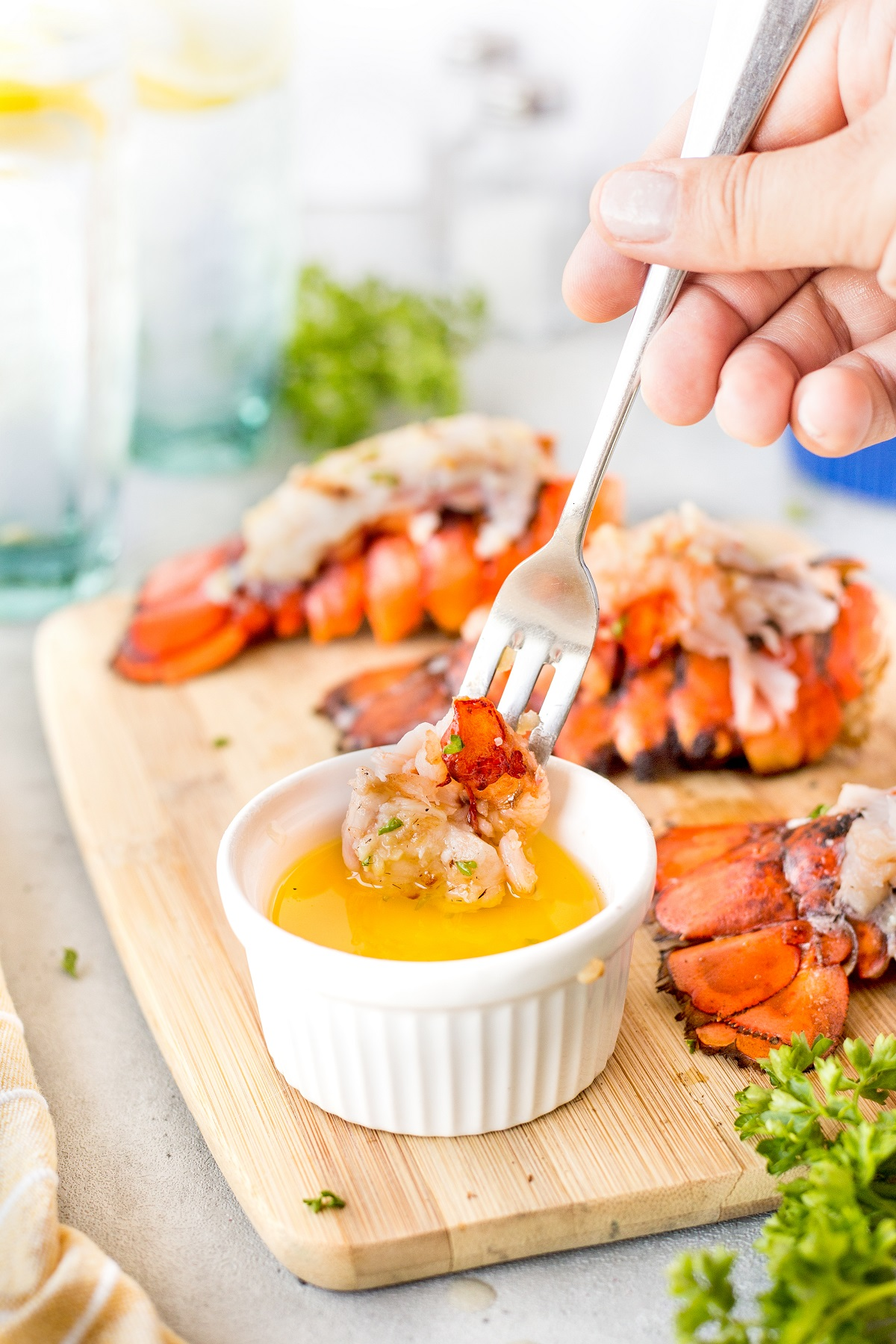 Fork full of lobster being dipped into a bowl of melted butter with 3 grilled lobster tails in the background
