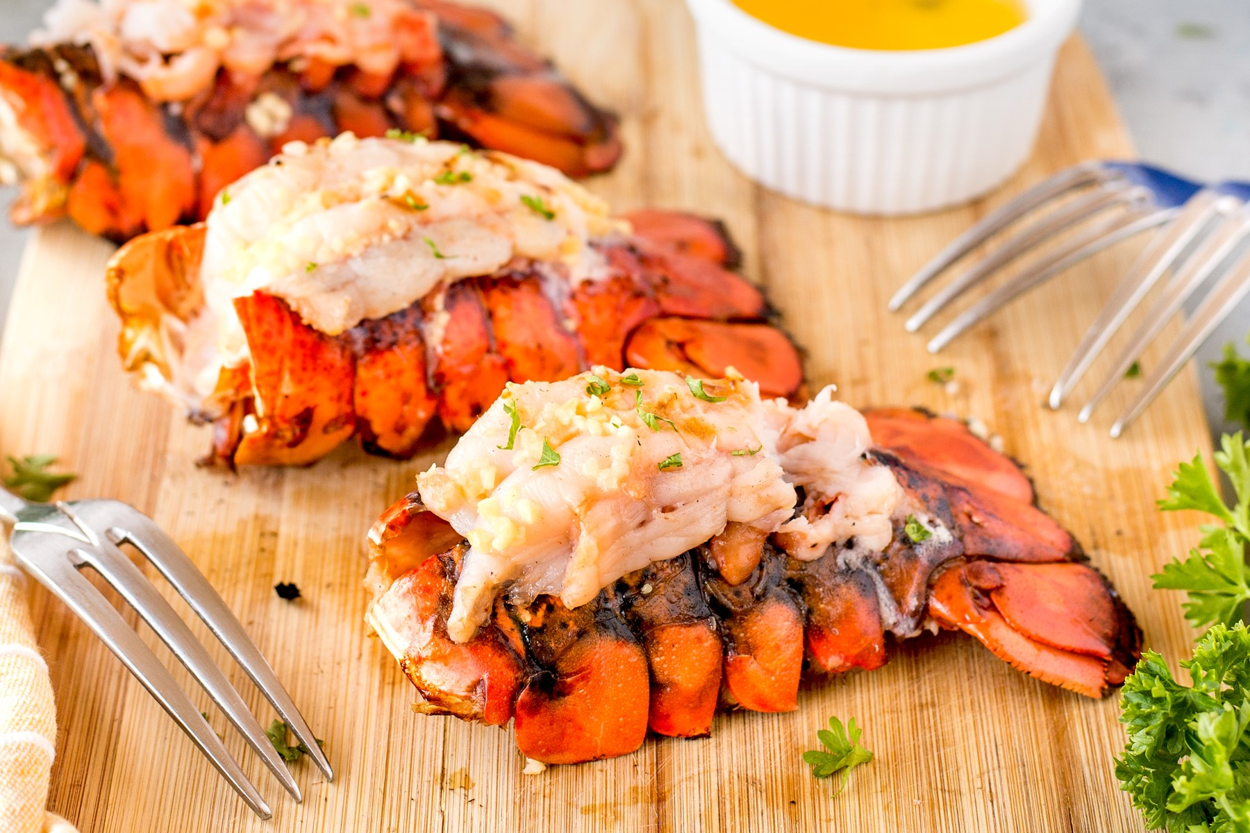 Grilled lobster tails on a wooden cutting board with a bowl of melted butter and 3 forks.