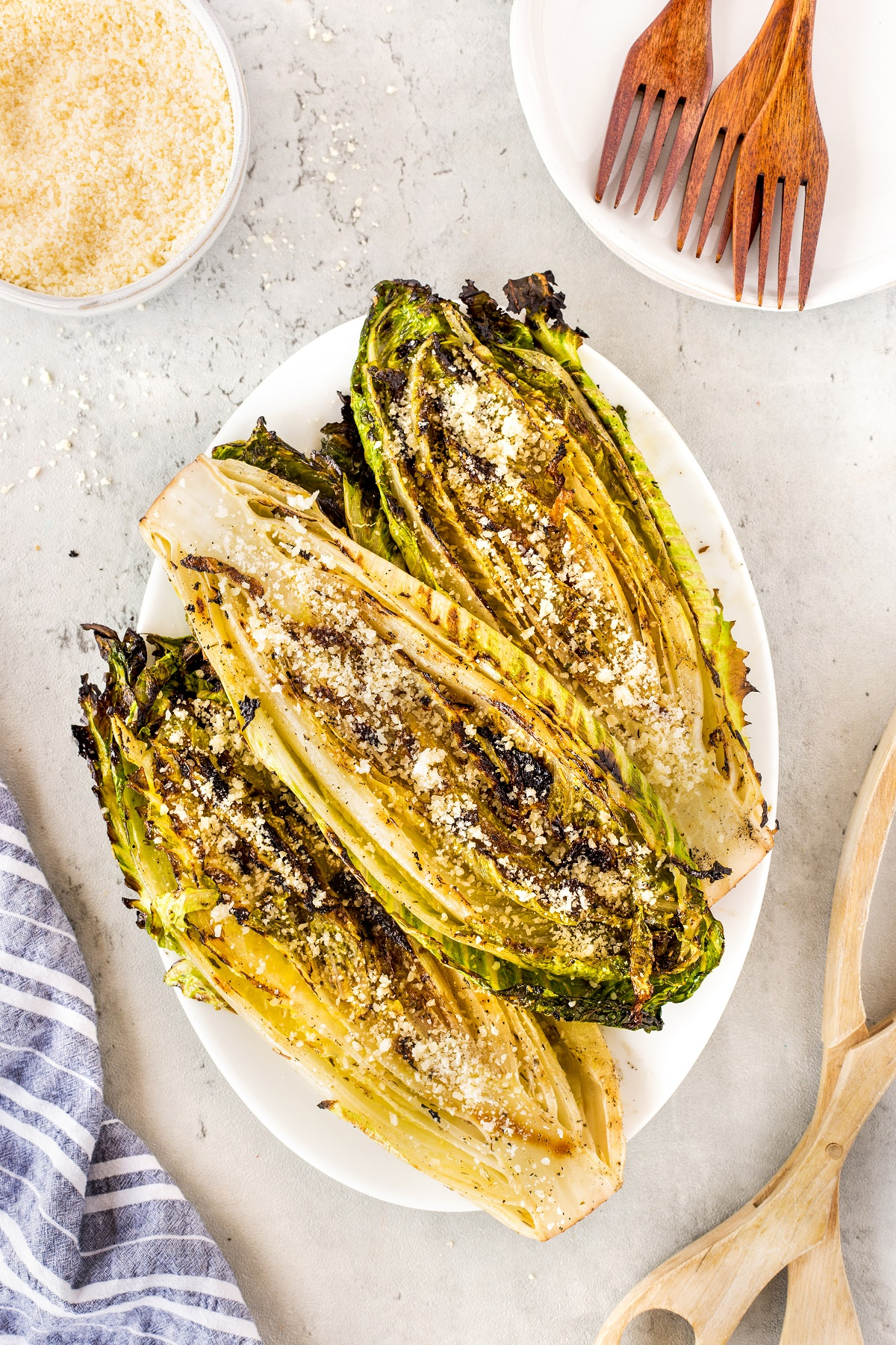 Grilled half heads of romaine lettuce with grated asiago cheese sprinkled on top on a white oval platter.