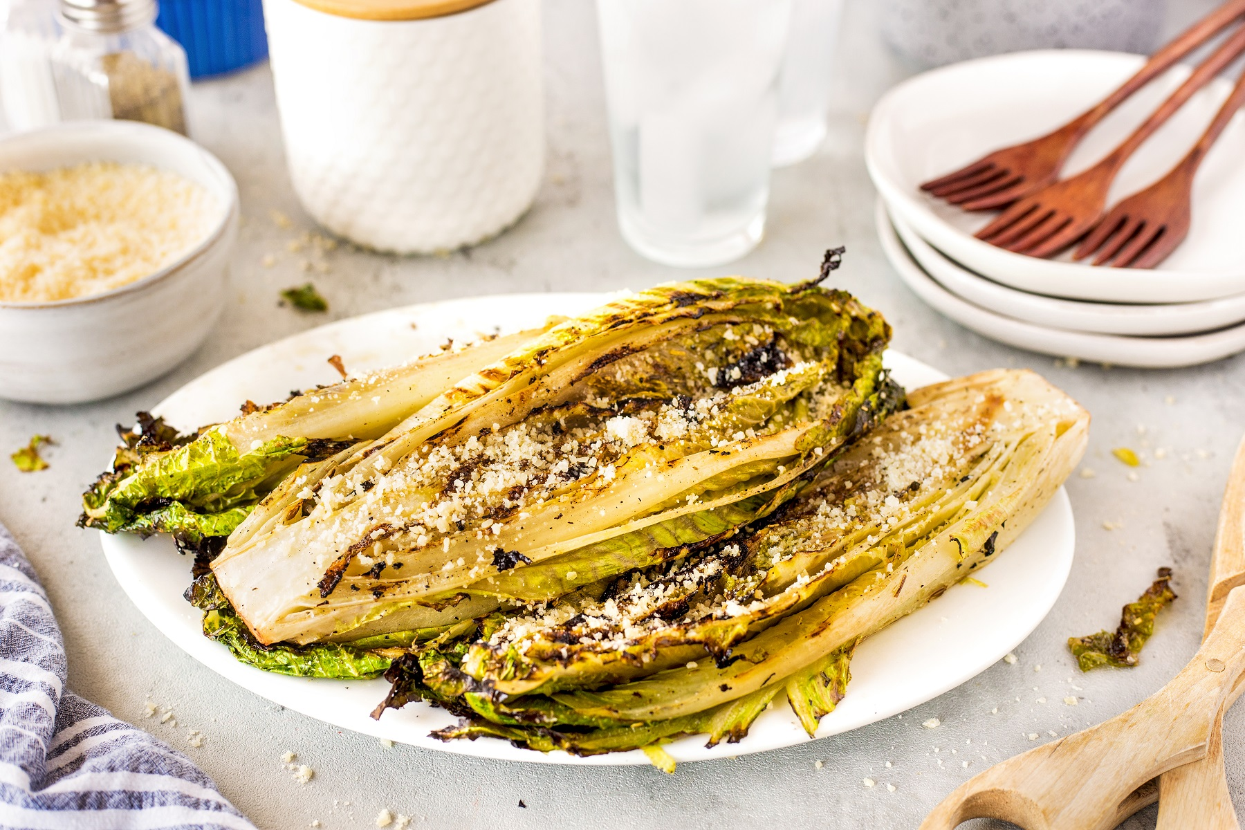 Grilled romaine heart halves on a white platter with grated cheese sprinkled on top.