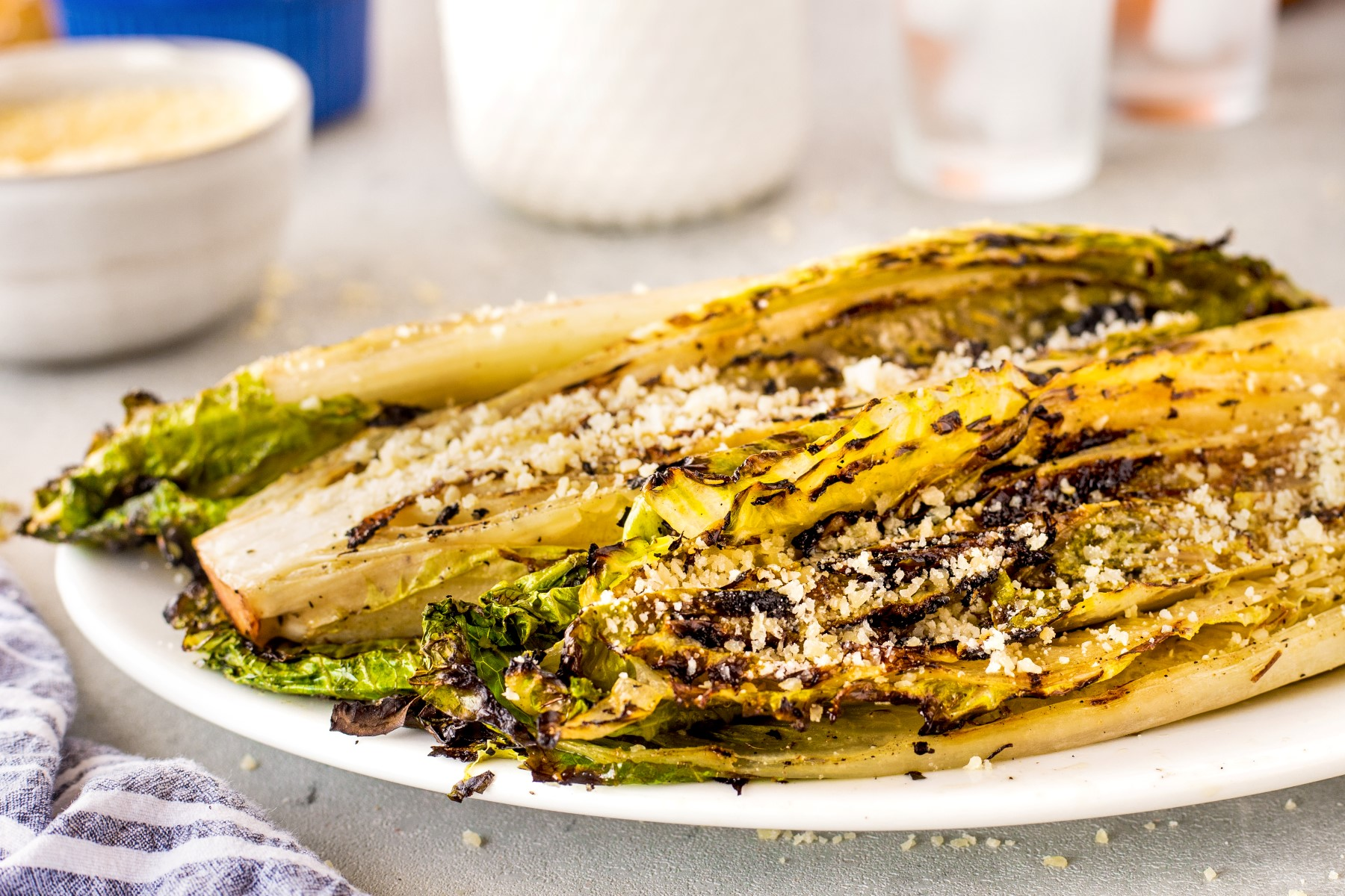 Grilled Romaine Hearts on a white platter with grated cheese sprinkled on top.