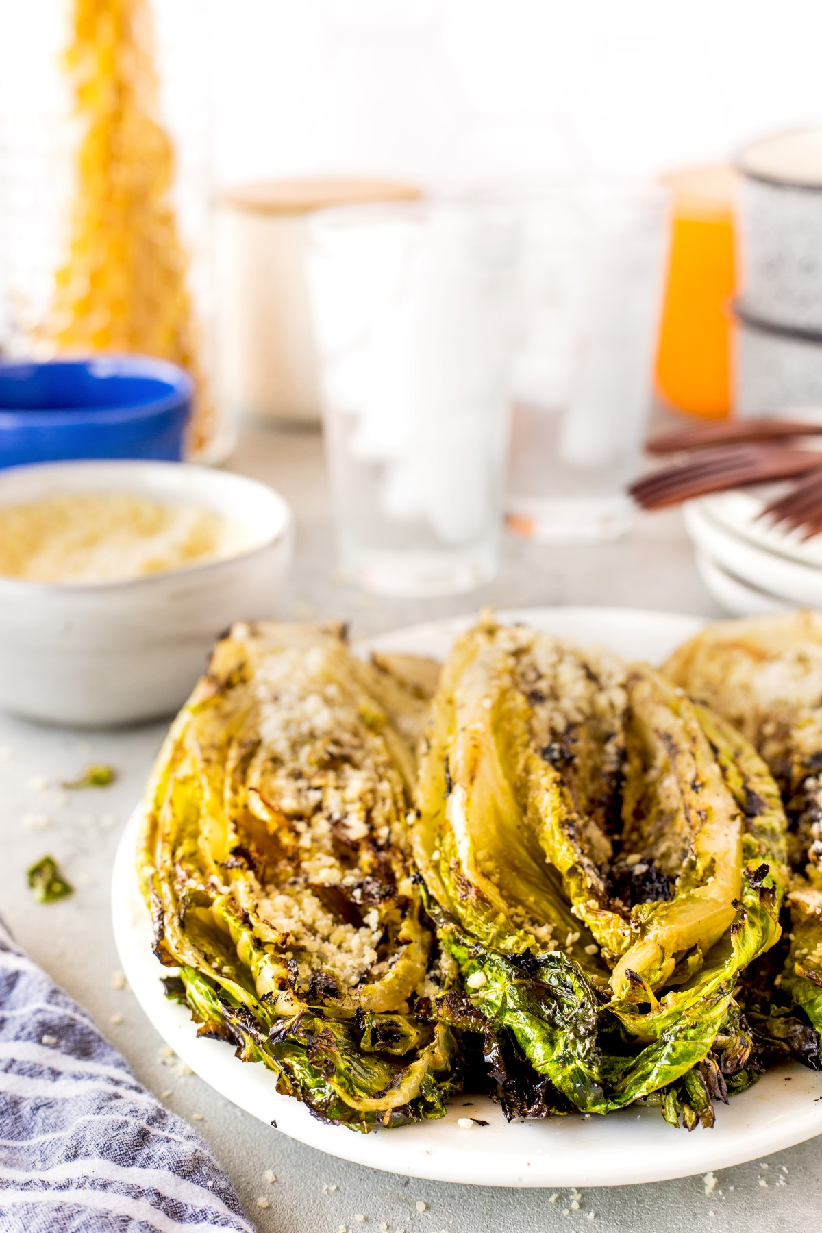 Grilled romaine lettuce halves on a white platter with grated asiago cheese sprinkled on top.