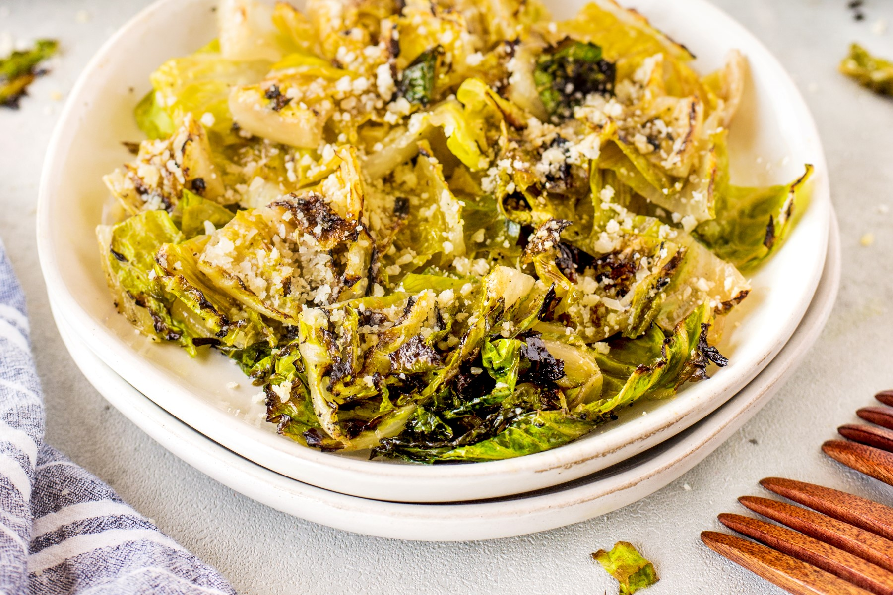 Grilled romaine lettuce chopped in a white bowl with asiago cheese sprinkled on top