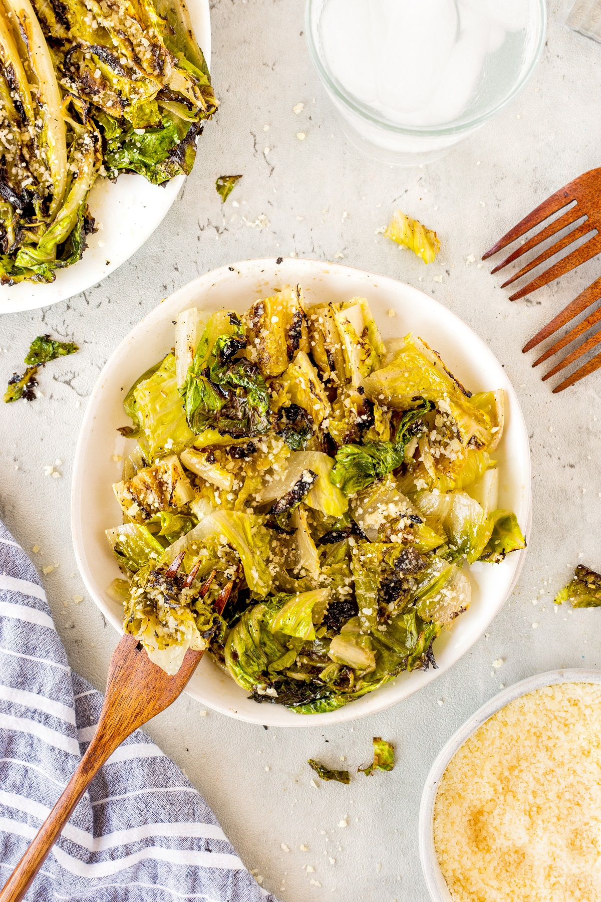 Grilled romaine lettuce chopped and place in a white serving bowl with grated asiago cheese sprinkled on top.
