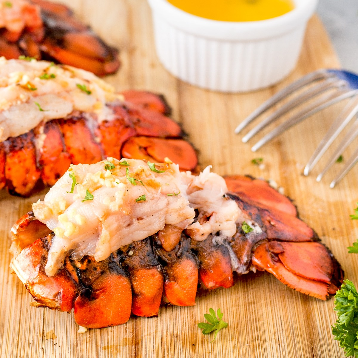 Grilled lobster tail on a wooden cutting board