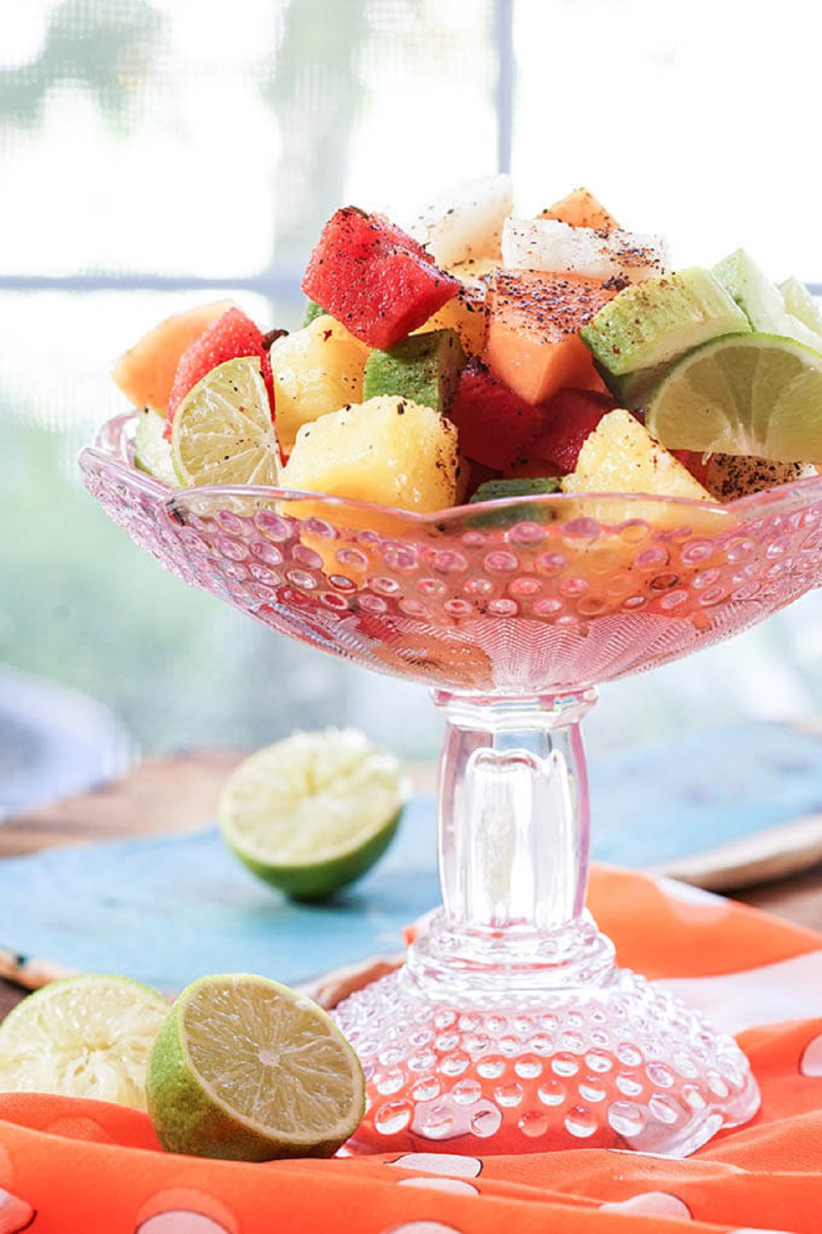 Mexican fruit salad in a tall pedestal dish with slices of lime on the table