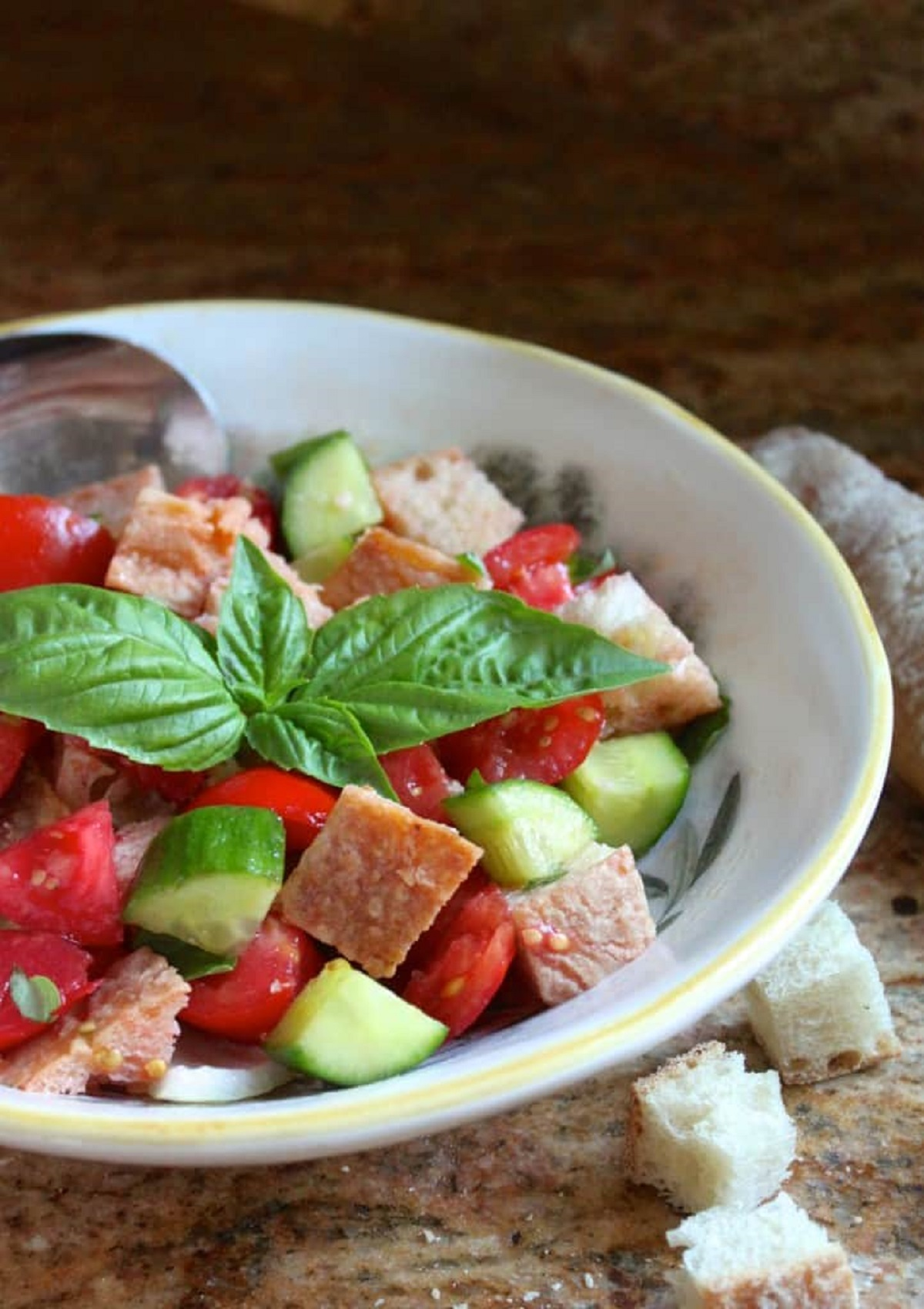 Panzanella, Italian bread and tomato salad in a white bowl garnished with fresh basil leaves.