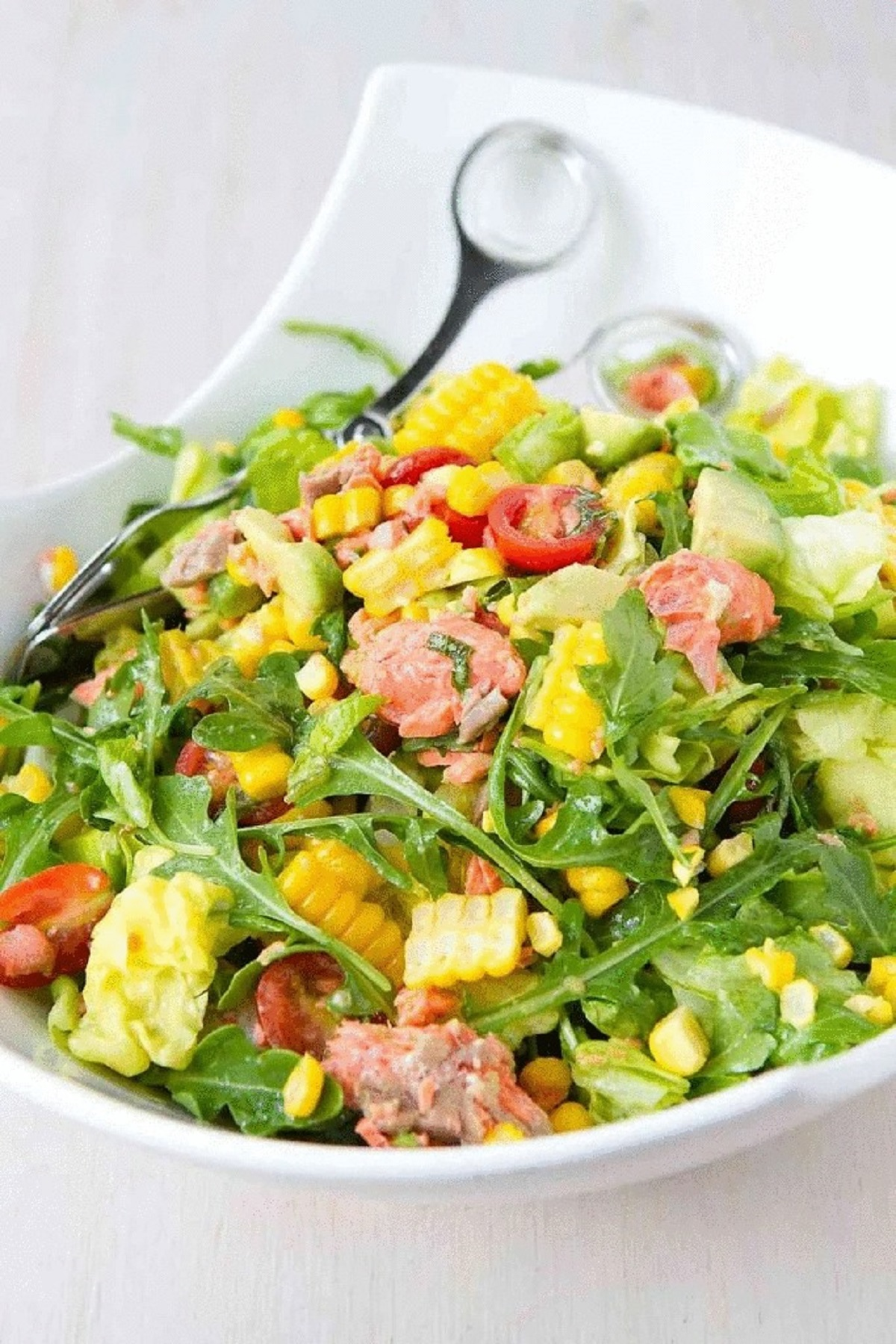Salmon chopped salad in a white serving bowl with corn and tomatoes.