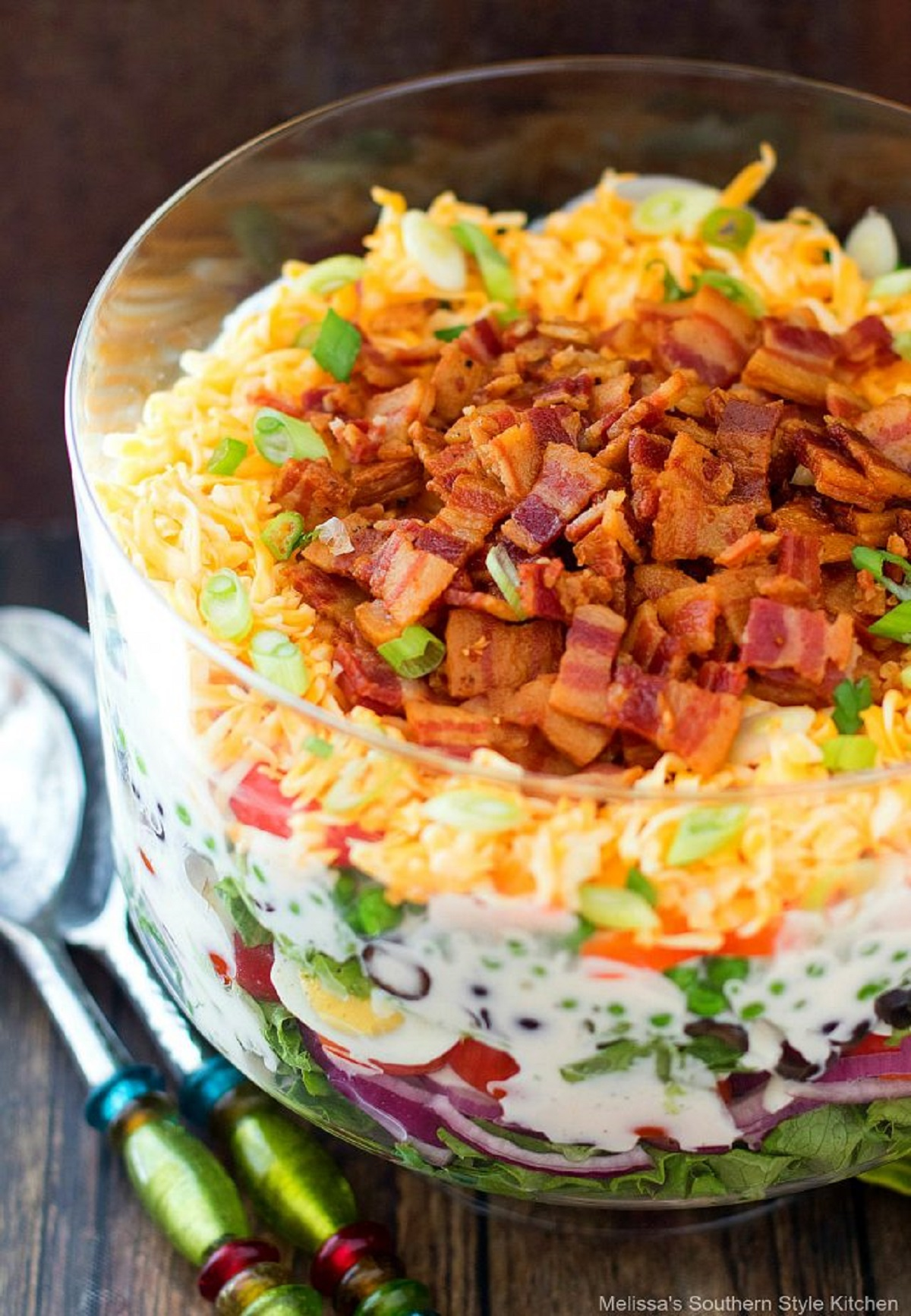 Seven layer salad in a trifle dish with serving spoons beside the bowl.