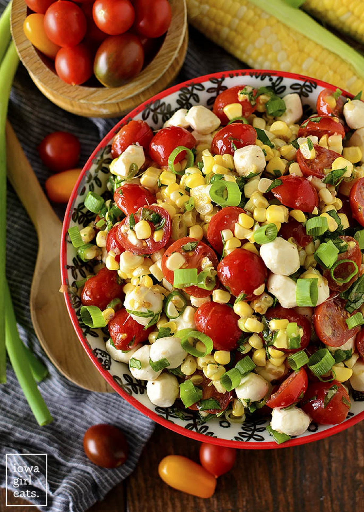 Sweet corn Caprese salad in a white an red bowl on a wooden board.