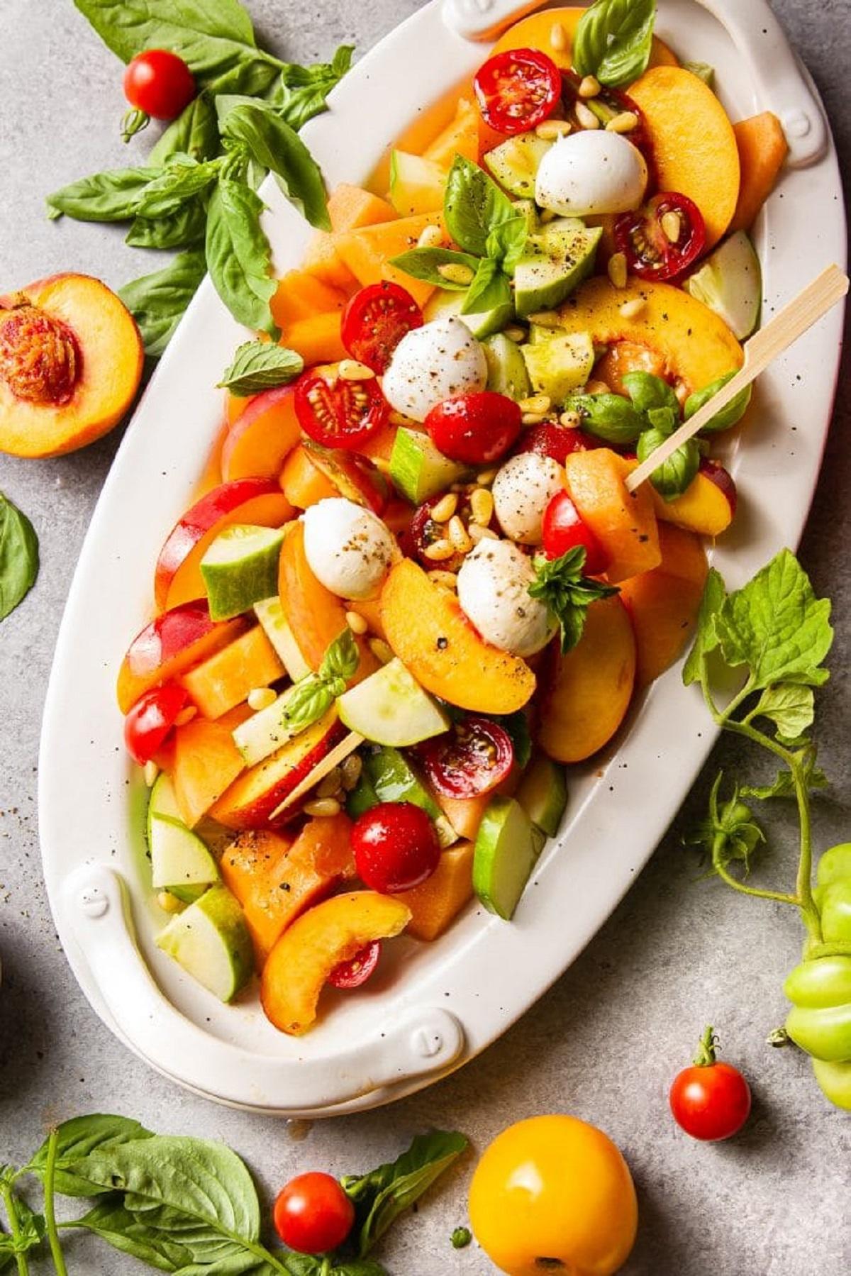 Cantaloupe peach fruit salad on a white oval platter