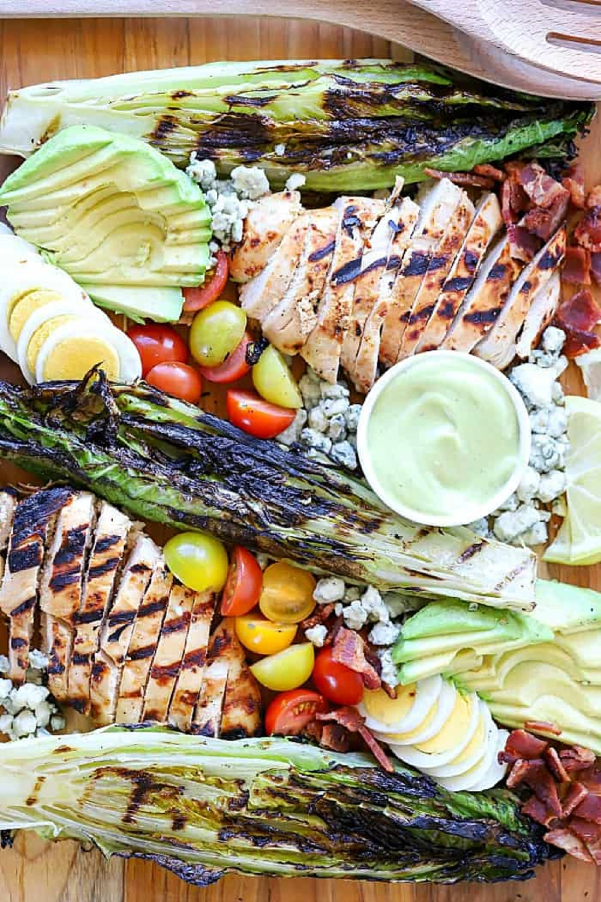 Grilled Cobb salad on a wooden board with a bowl of avocado dressing.