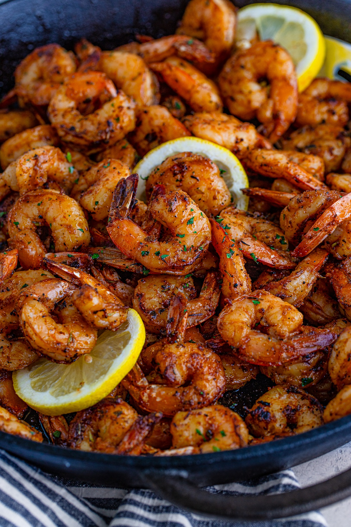 Blackened shrimp in a cast-iron pan with slices of lemon on a blue and white towel