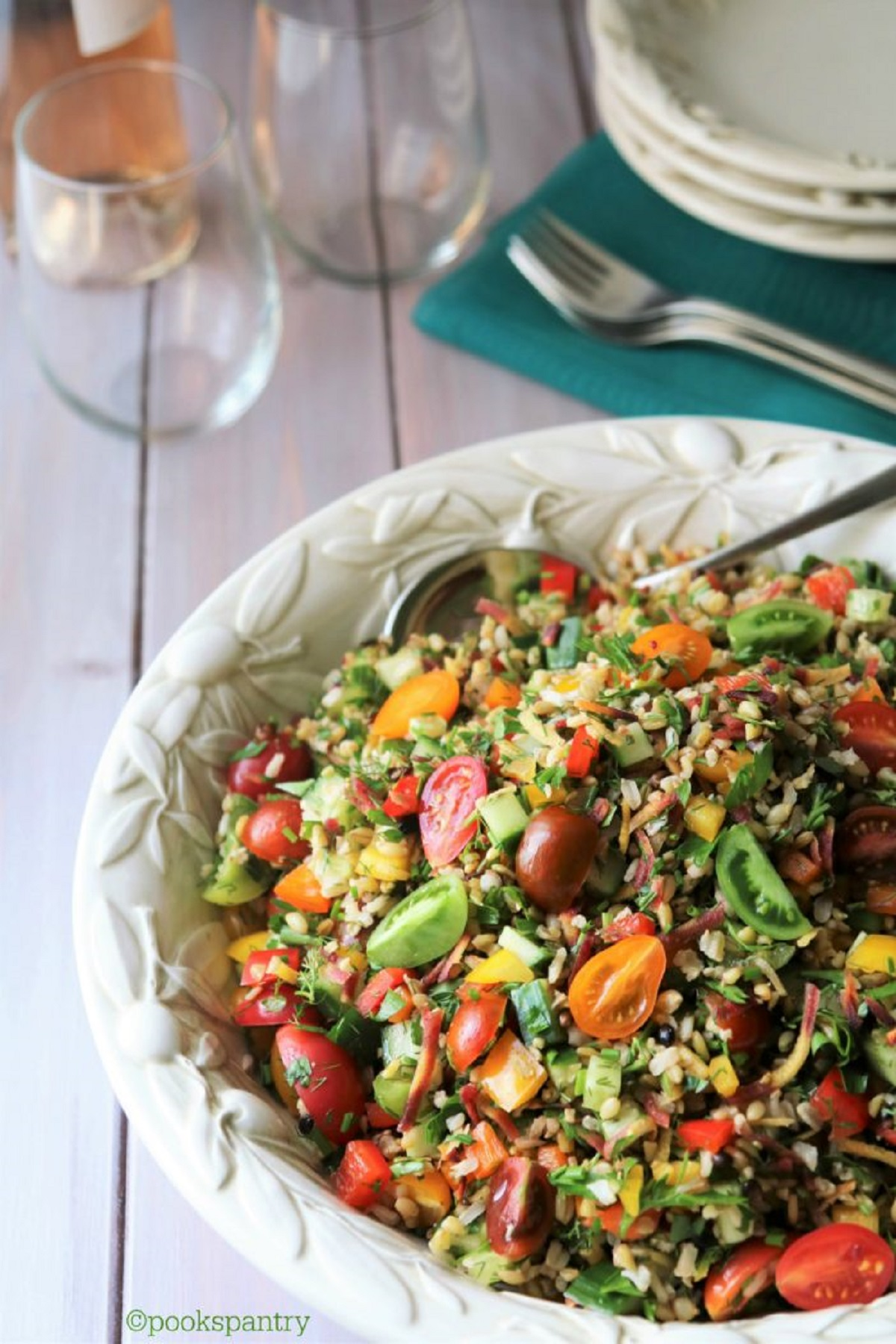 Summer grain salad with tomatoes in a large white serving bowl.