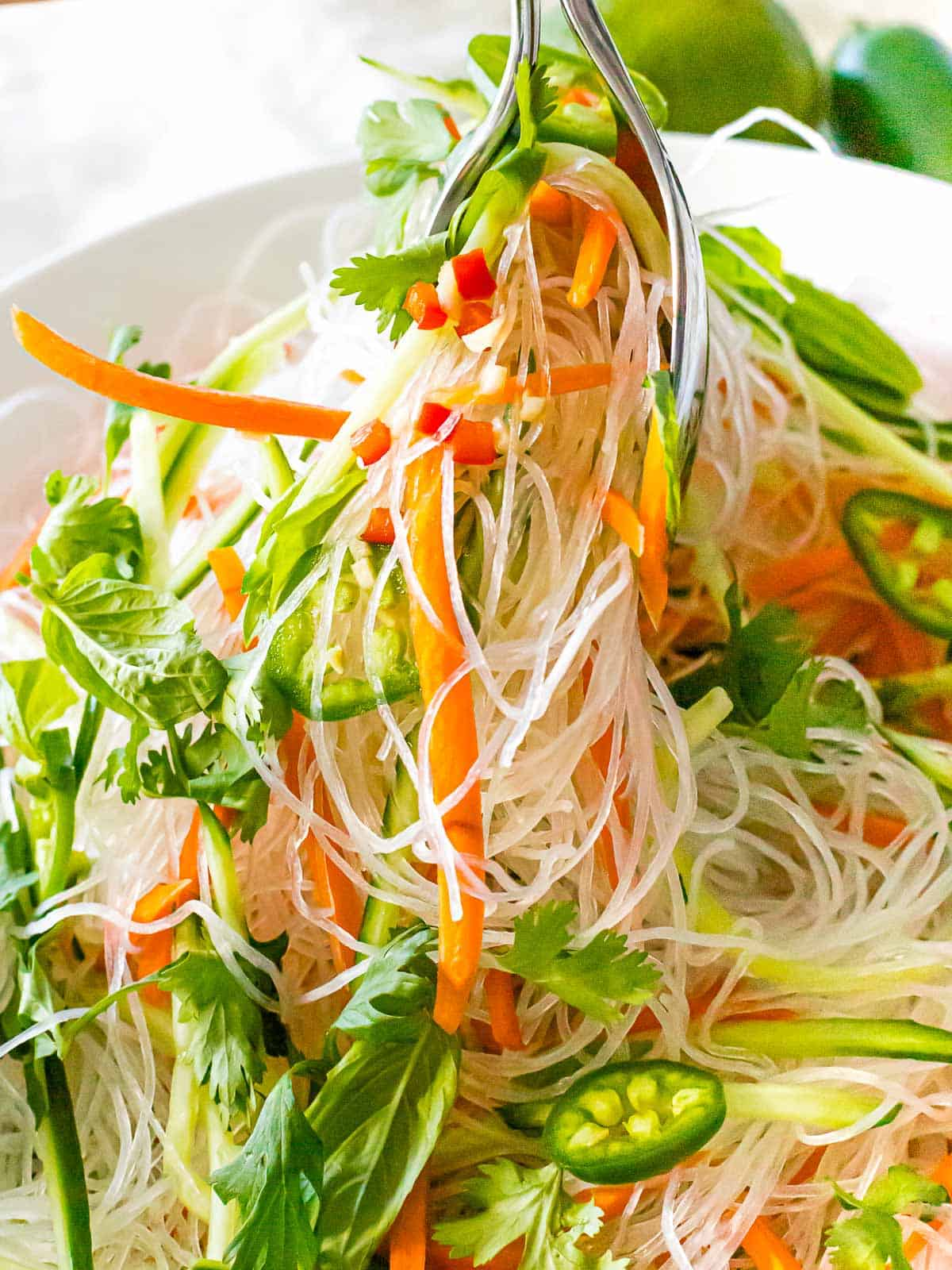 Vietnamese noodle salad with strips of carrot, parsley & basil leaves ad a slice of jalapeno.