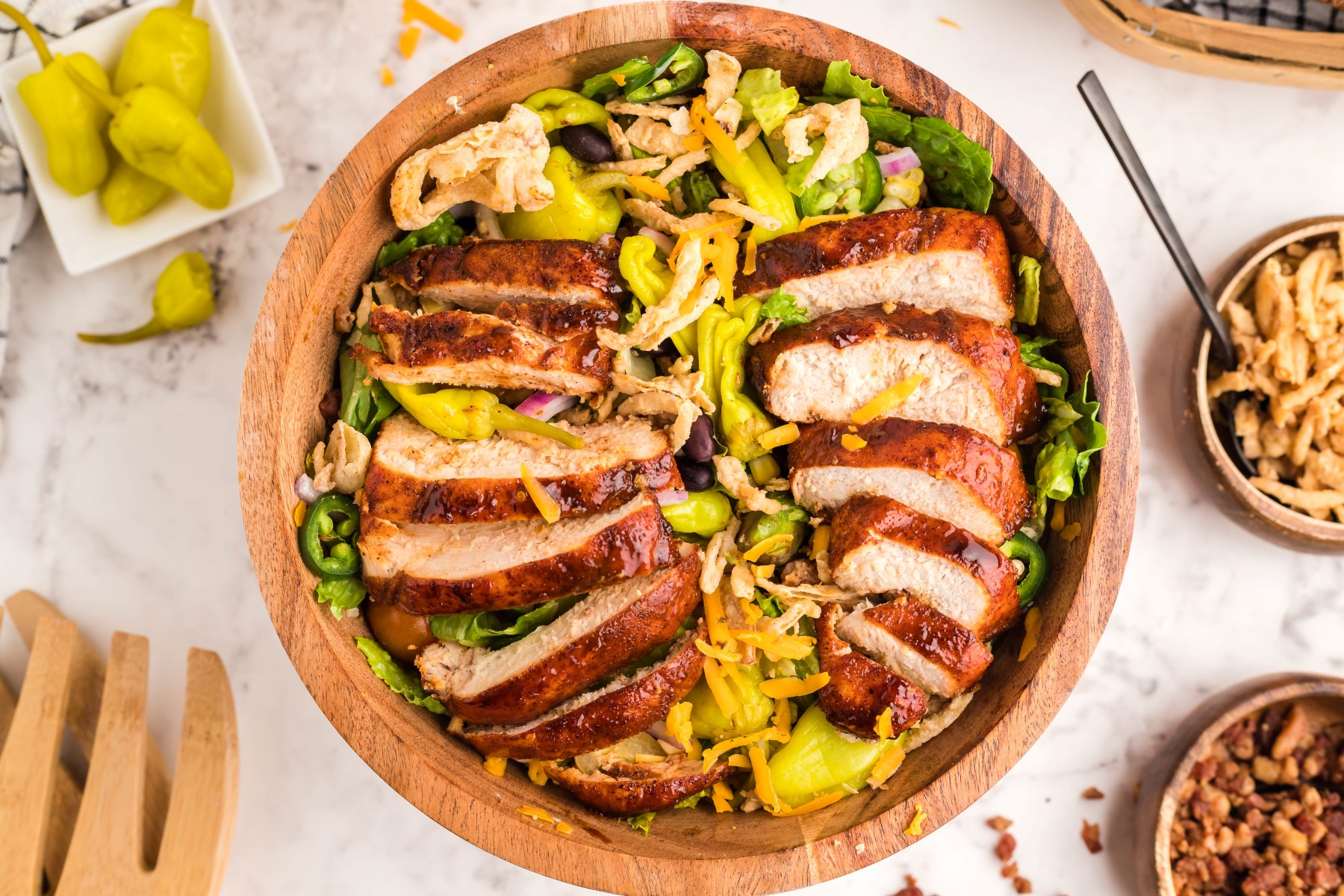 wooden salad bowl filled with grilled chicken salad with ingredients in small bowls around the large salad bowl.
