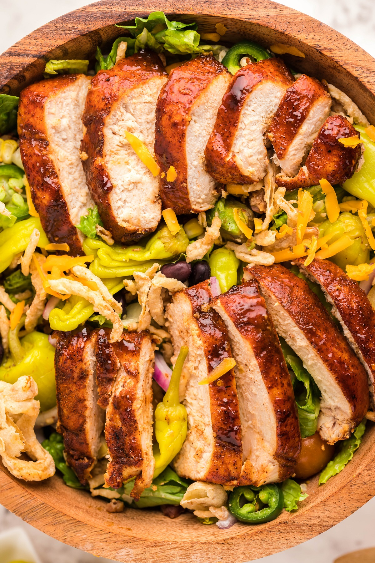 Grilled Chicken Salad in a large wooden salad bowl topped with fried onions, grated cheese, jalapenos and pepperoncini.