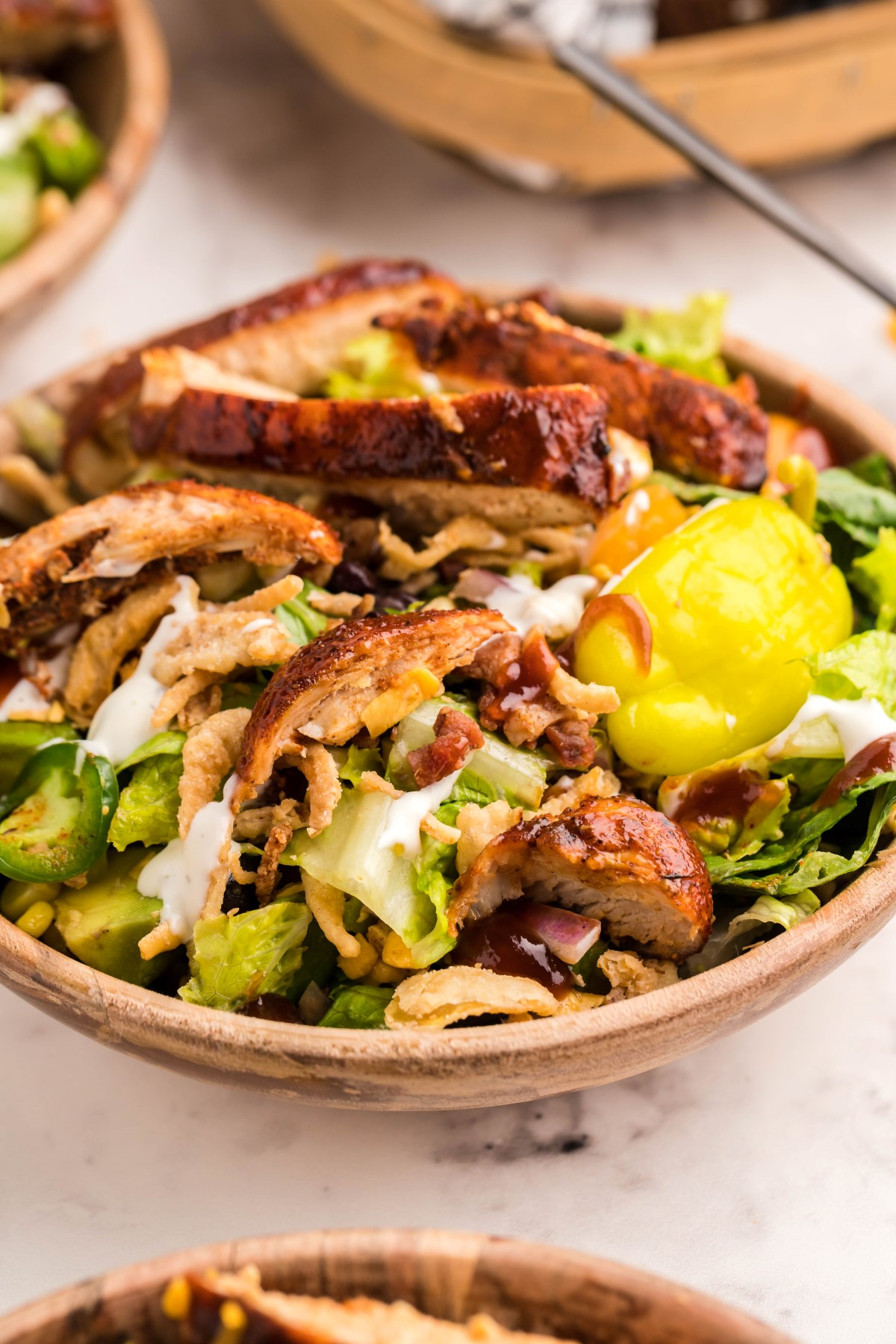 Individual wooden salad bowl filled with grilled chicken salad.