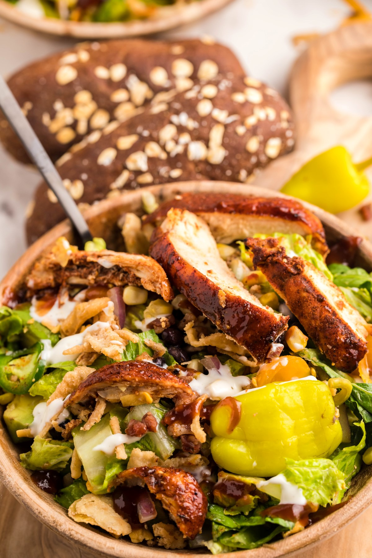 Bowl of grilled chicken salad with a fork and bread in the background.