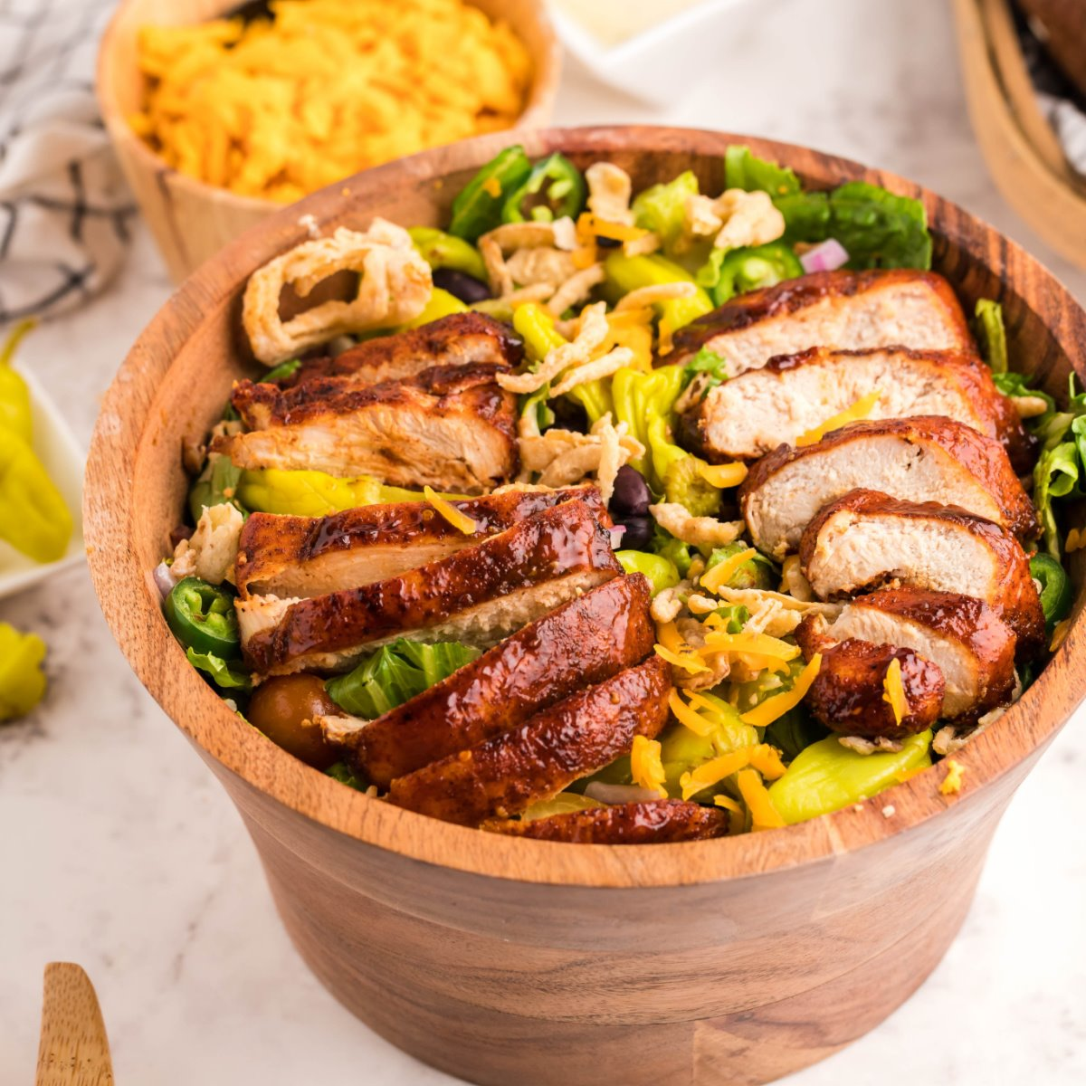 Grilled chicken salad in a large wooden salad bowl on a marble surface.
