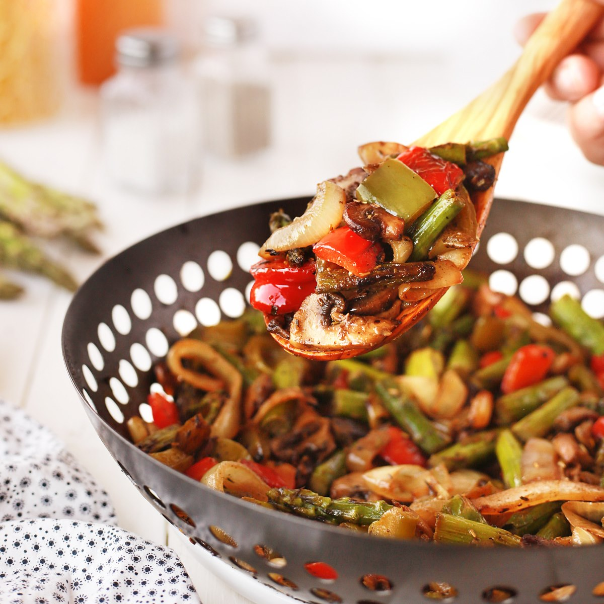 BBQ wok vegetables being spooned out of the BBQ wok with a wooden spoon