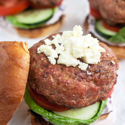 Greek turkey burger with the top bun off and crumbled feta cheese on the burger