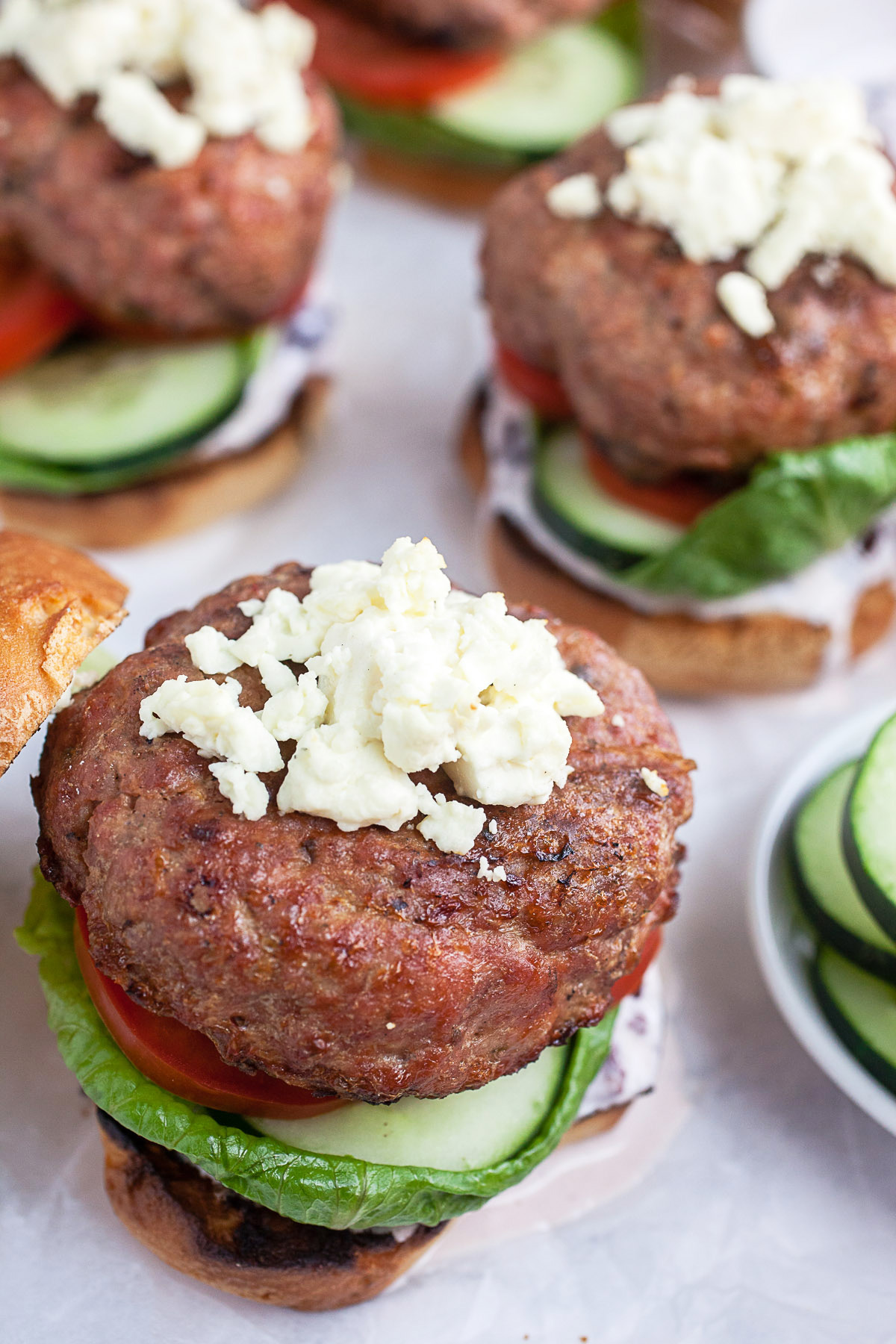Grilled Greek turkey burger on a bun bottom with lettuce, cucumber and tomato. Crumbled feta is on top of the patty.