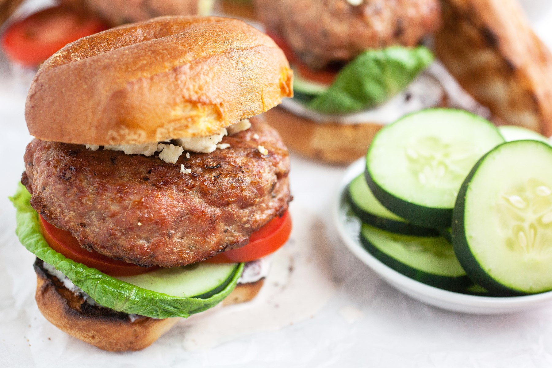 Greek turkey burger with feta, cucumber and tomato slices and lettuce sitting on a white counter.
