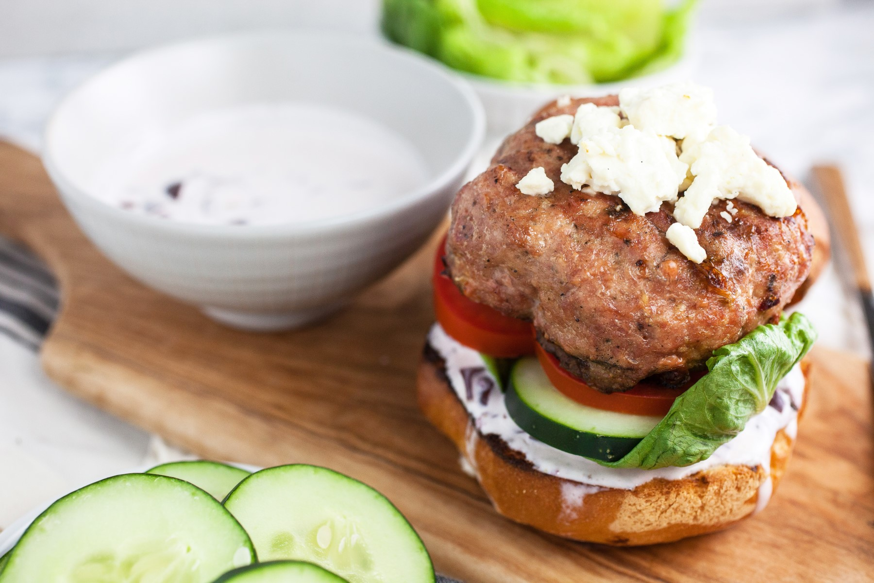 Greek Turkey Burger on a bun with no top garnished with tomato, cucumber, lettuce, Kalamata olive aioli and crumbled feta cheese