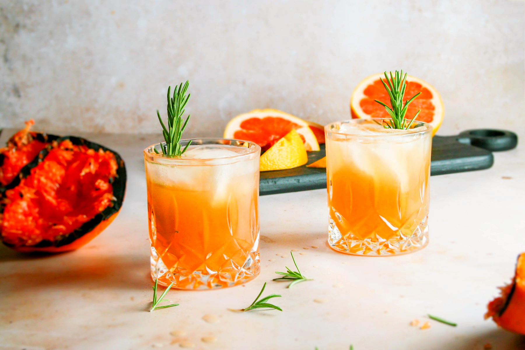 2 old fashion glasses with grilled grapefruit greyhounds over ice and sprigs of rosemary in each .
