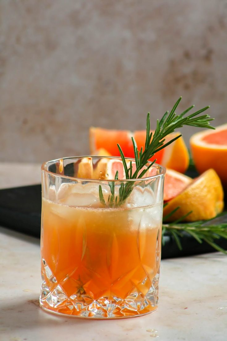 Grilled grapefruit greyhound cocktail in an old fashion glass with a sprig of rosemary