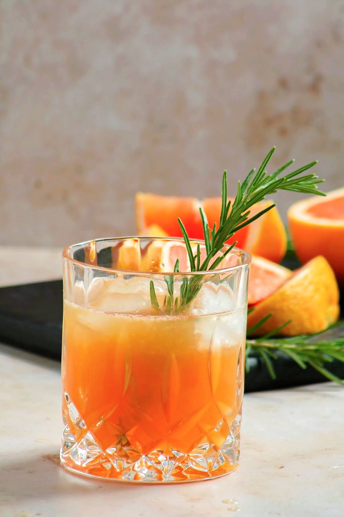 Grilled grapefruit greyhound cocktail in an old fashion glass over ice with a sprig of rosemary