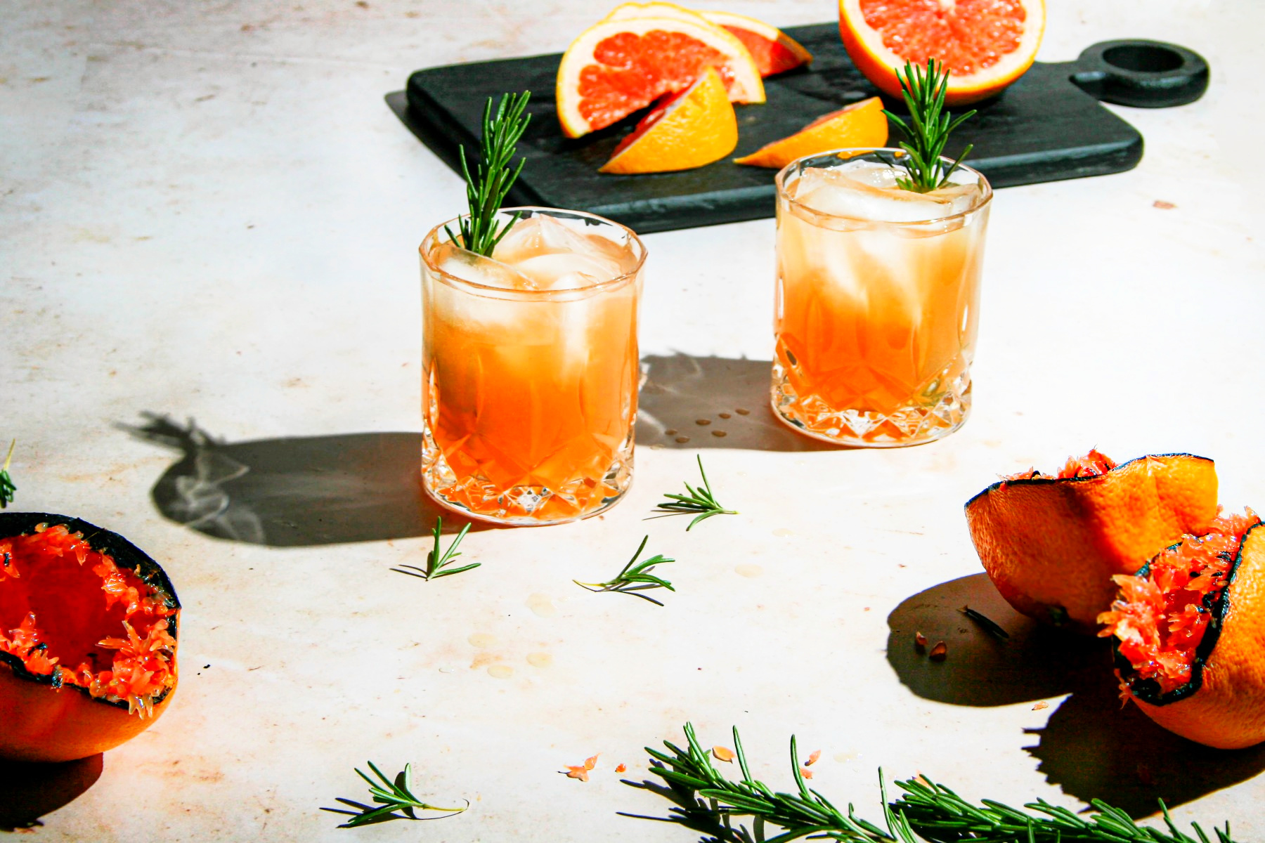 2 old fashion glasses filled with grilled grapefruit greyhounds over ice with rosemary sprigs and grilled grapefruit halves and fresh smiles in the background