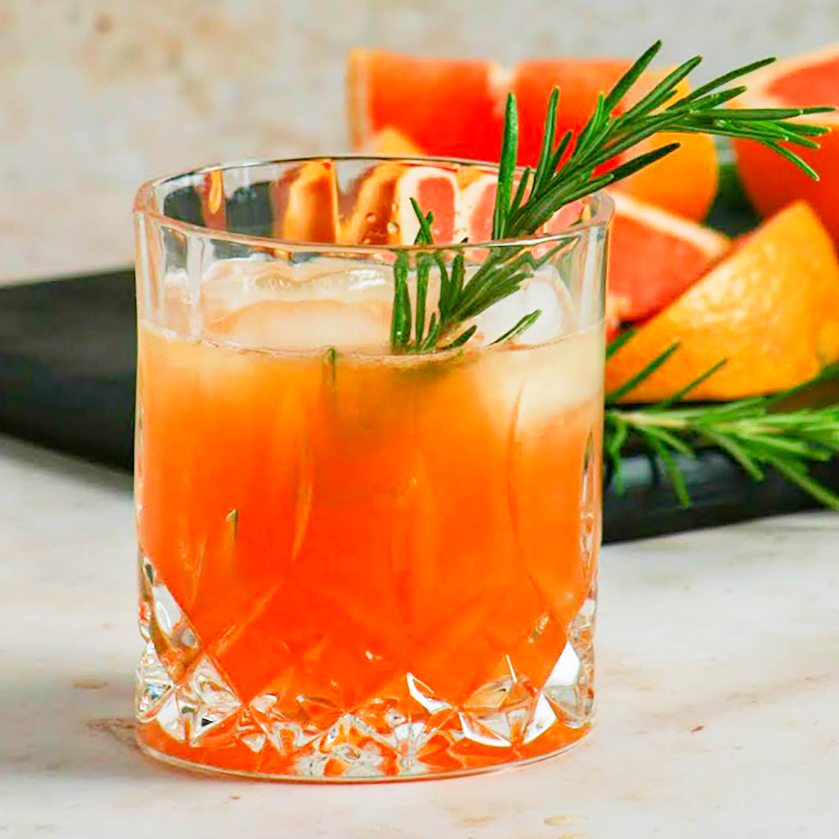 old fashion cocktail glass filled with a grilled grapefruit greyhound cocktail with a sprig of fresh rosemary over ice.