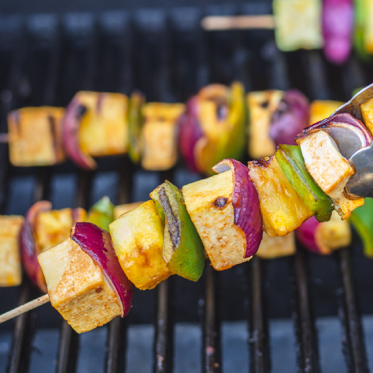 Close up of Hawaiian grilled tofu skewer over a grill.
